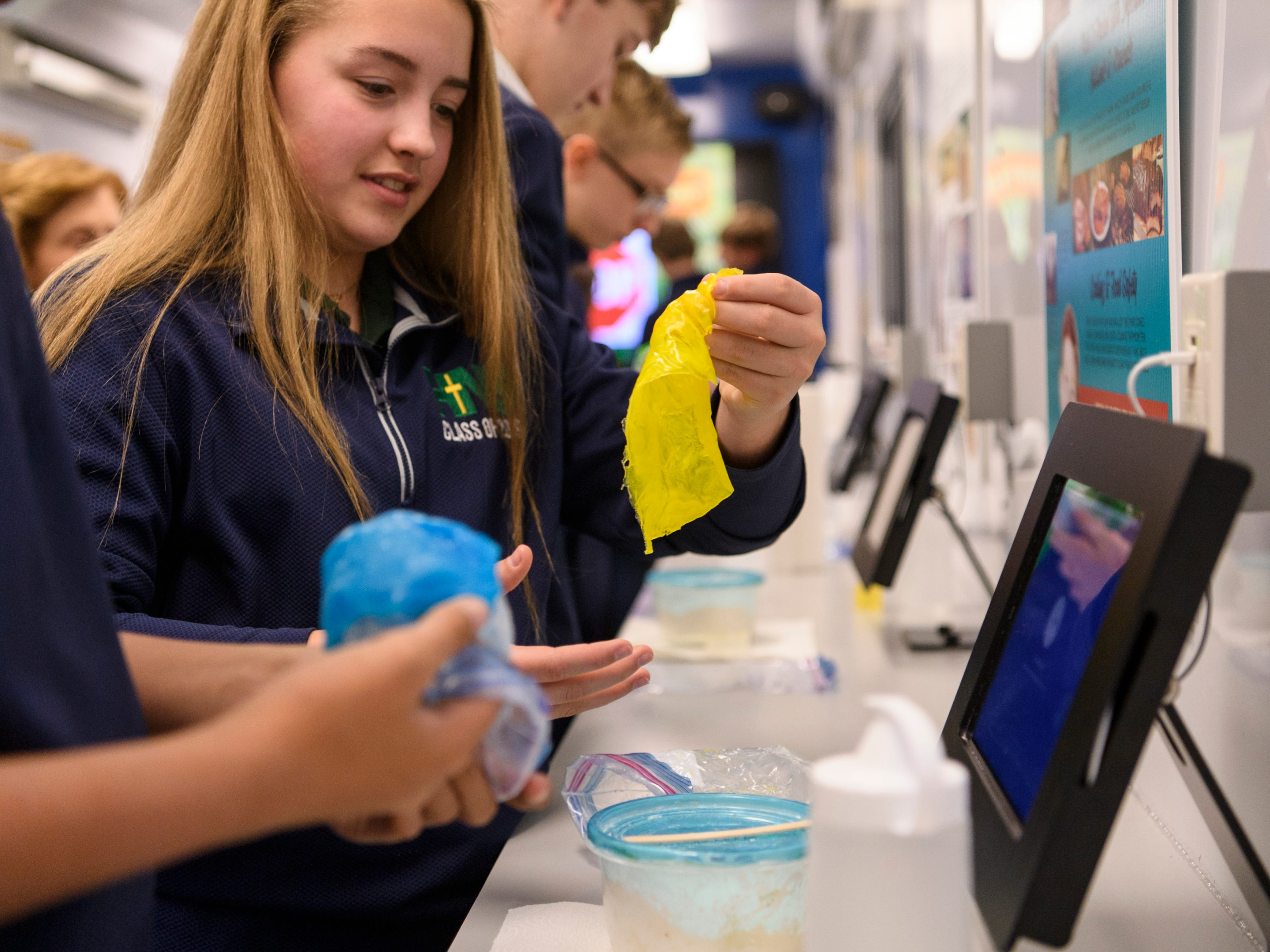 Eighth-Grader Tori Allinder rolls out a colorful piece of biodegradable corn plastic that she made while conducting a science experiment inside the Kentucky Department of Agriculture Mobile Science Activity Center parked outside of Holy Name School in Henderson, Ky., Wednesday, Jan. 9, 2019.
