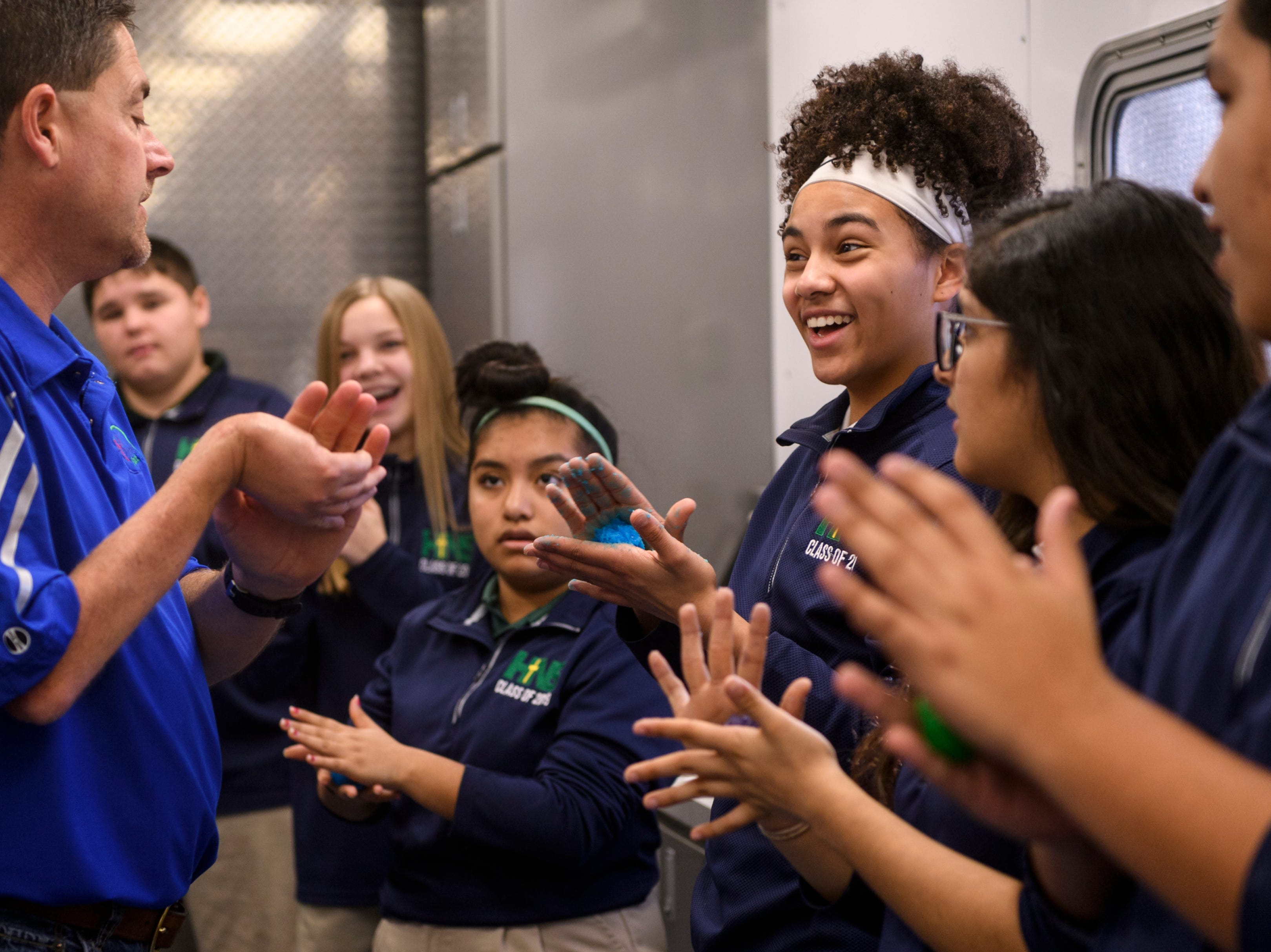 Eighth-grader Jolie Caron, center right, and her classmates shape biodegradable corn plastic into bouncy balls after following instructions from Program Coordinator Jason Hodge, left, inside the Kentucky Department of Agriculture Mobile Science Activity Center parked outside of Holy Name School in Henderson, Ky., Wednesday, Jan. 9, 2019. Hodge hauls the 44-foot trailer, that can accommodate up to 30 students at a time, to schools around Kentucky to teach hand-on science experiments. Holy Name School worked in partnership with Henderson Community College's Agriculture and Education departments to bring the bus to the school for several school days.