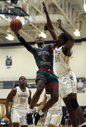 Lawrence North Wildcats Jared Hankins (5) drives on Decatur Central Hawks Nehemiah Jones (24) during the Marion County Basketball Tournament at Decatur Central High School on Tuesday, Jan. 8, 2019.