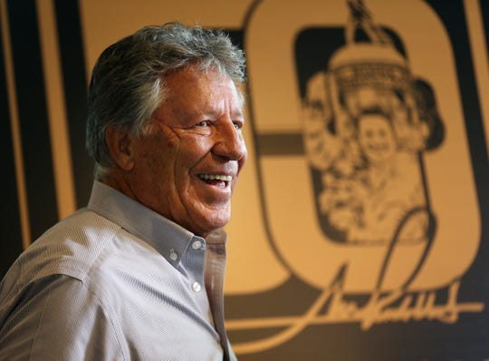 Indy 500 champion Mario Andretti poses for photos with the official logo celebrating the 50th anniversary of Andretti's winning of the Indy 500, during a press conference at Indianapolis Motor Speedway, Wednesday, Jan. 9, 2019.