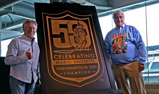 Indy 500 champion Mario Andretti, left, and Hulman & Company CEO Mark Miles unveil the official logo celebrating the 50th anniversary of Andretti's winning of the Indy 500, during a press conference at Indianapolis Motor Speedway, Wednesday, Jan. 9, 2019.