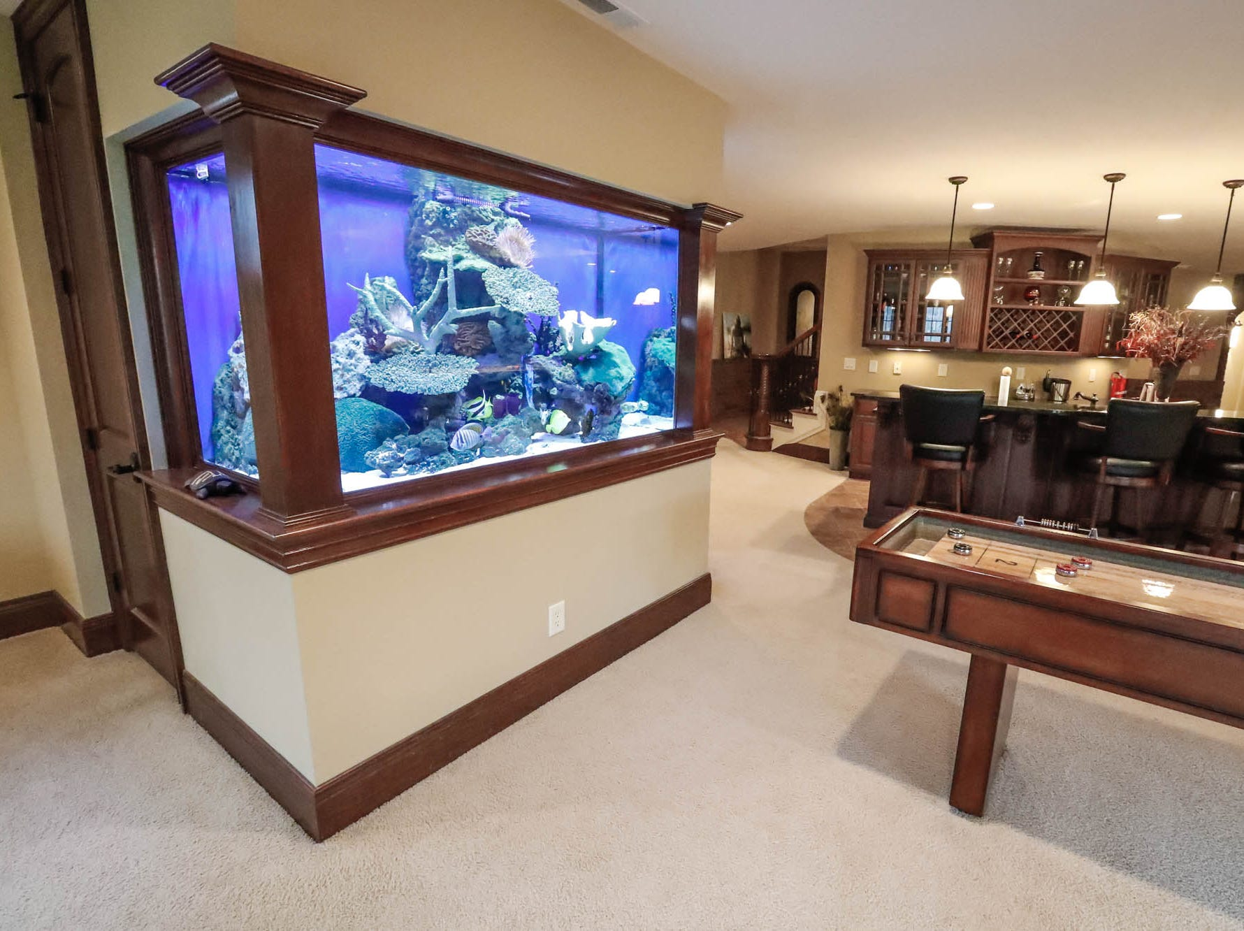 The basement of a traditional $2m home up for sale in Bargersville Ind., features a 500-gallon aquarium, shuffleboard table, bar, fireplace and home theatre room on Wednesday, Jan. 9, 2019. The home sits on 8.1 acres.