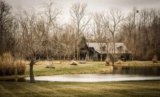 A one-hundred-year-old barn moved from northern Indiana sits behind a traditional style $2m home with elements of French country and Tuscan influence up for sale in Bargersville Ind. on Wednesday, Jan. 9, 2019. The house and barn sit on 8.1 acres and features two horse stalls and a man cave with a vintage stove.