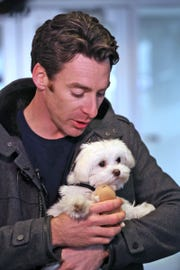 IndyCar driver Simon Pagenaud, a dog lover, holds Pistachio.