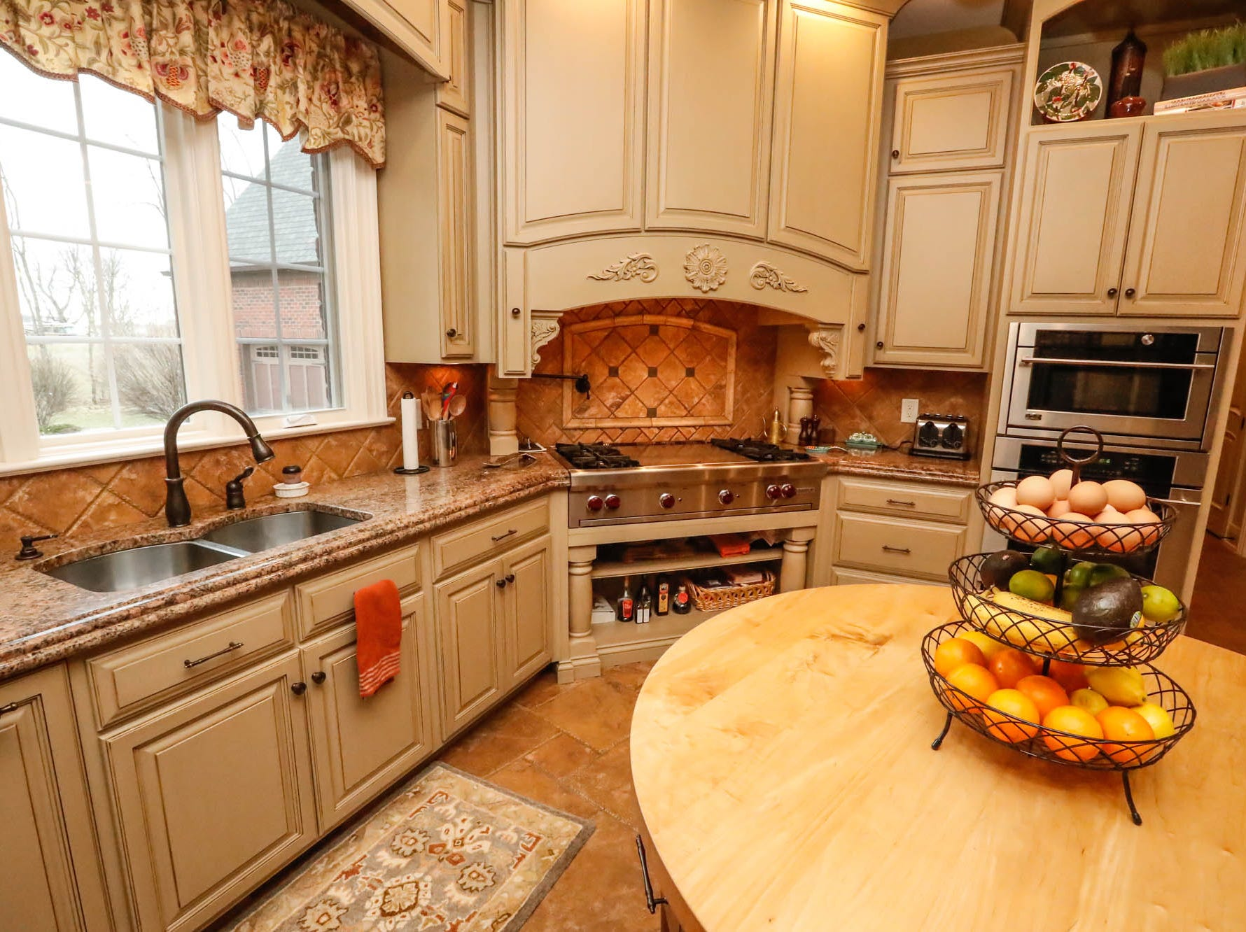 The open plan kitchen features a round chopping island,  rustic Tuscan tile, and a Wolf stove with griddle in a traditional $2m home up for sale in Bargersville Ind. on Wednesday, Jan. 9, 2019. The house sits on 8.1 acres.