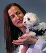 Pistachio, a Maltese-mix puppy, with Tara Harris, a child abuse specialist and pediatrician at Riley Hospital for Children at IU Health.