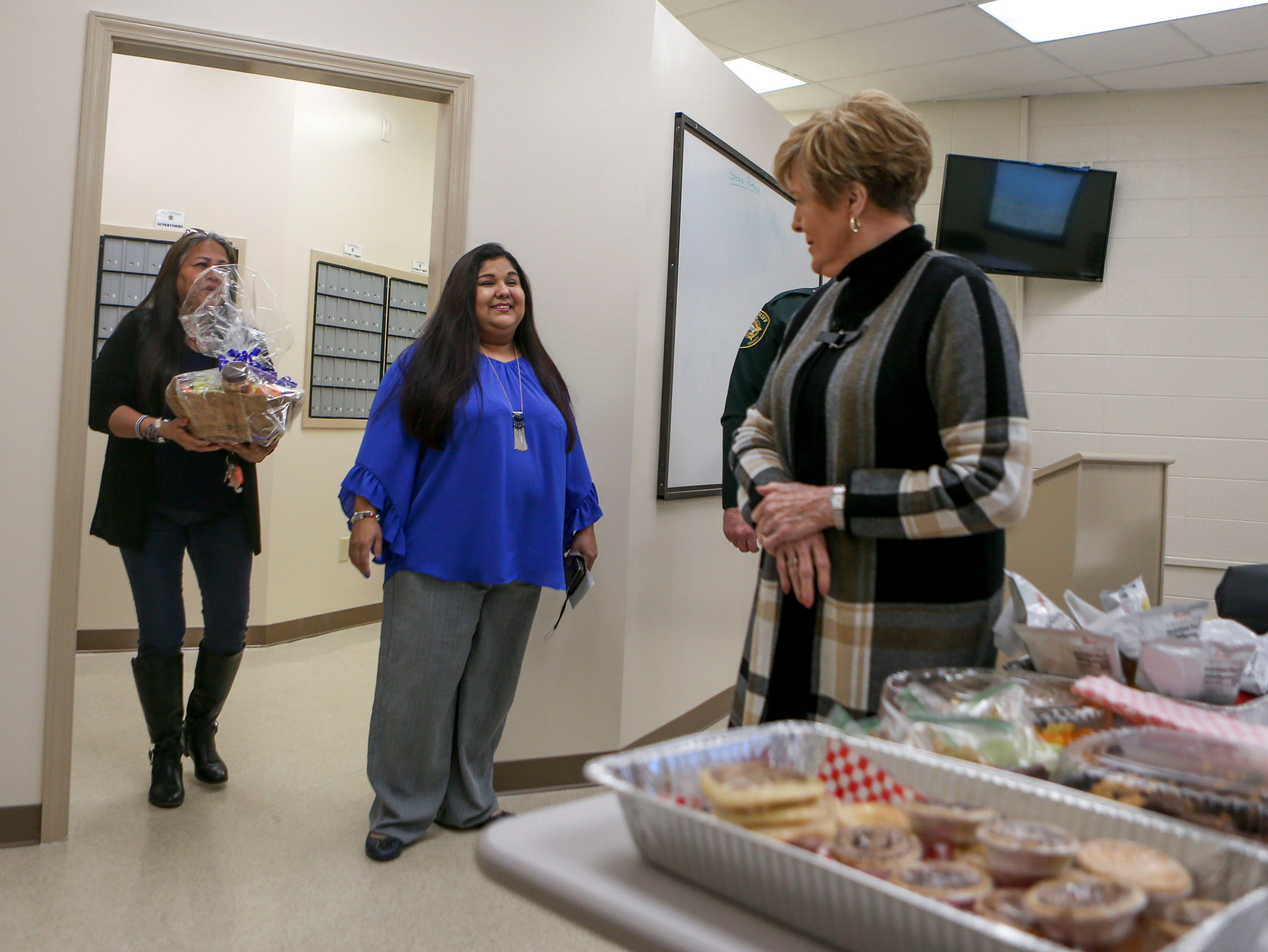 Emily Crabtree, right, welcomes Estella Villalobos, center, and Maria A. Vela, the respective aunt and mother of Rosemary Vela, a deputy for MCSO that died in the line of duty three years ago, at Madison County Sheriff's Office in Denmark, Tenn., on Wednesday, Jan. 9, 2019. Crabtree came out to deliver snacks for deputies on National Law Enforcement Day and Villalobos and Vela return every year.