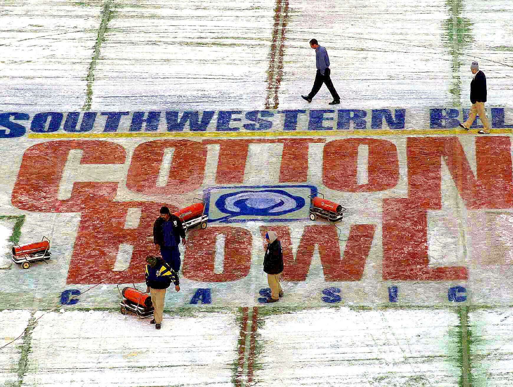 Cotton Bowl officials worked Monday morning to clear snow from the field from a 1/2-inch snow and ice storm which hit Dallas New Year's Eve. the Cotton Bowl game was scheduled to begin at 10:16 a.m. in Dallas.