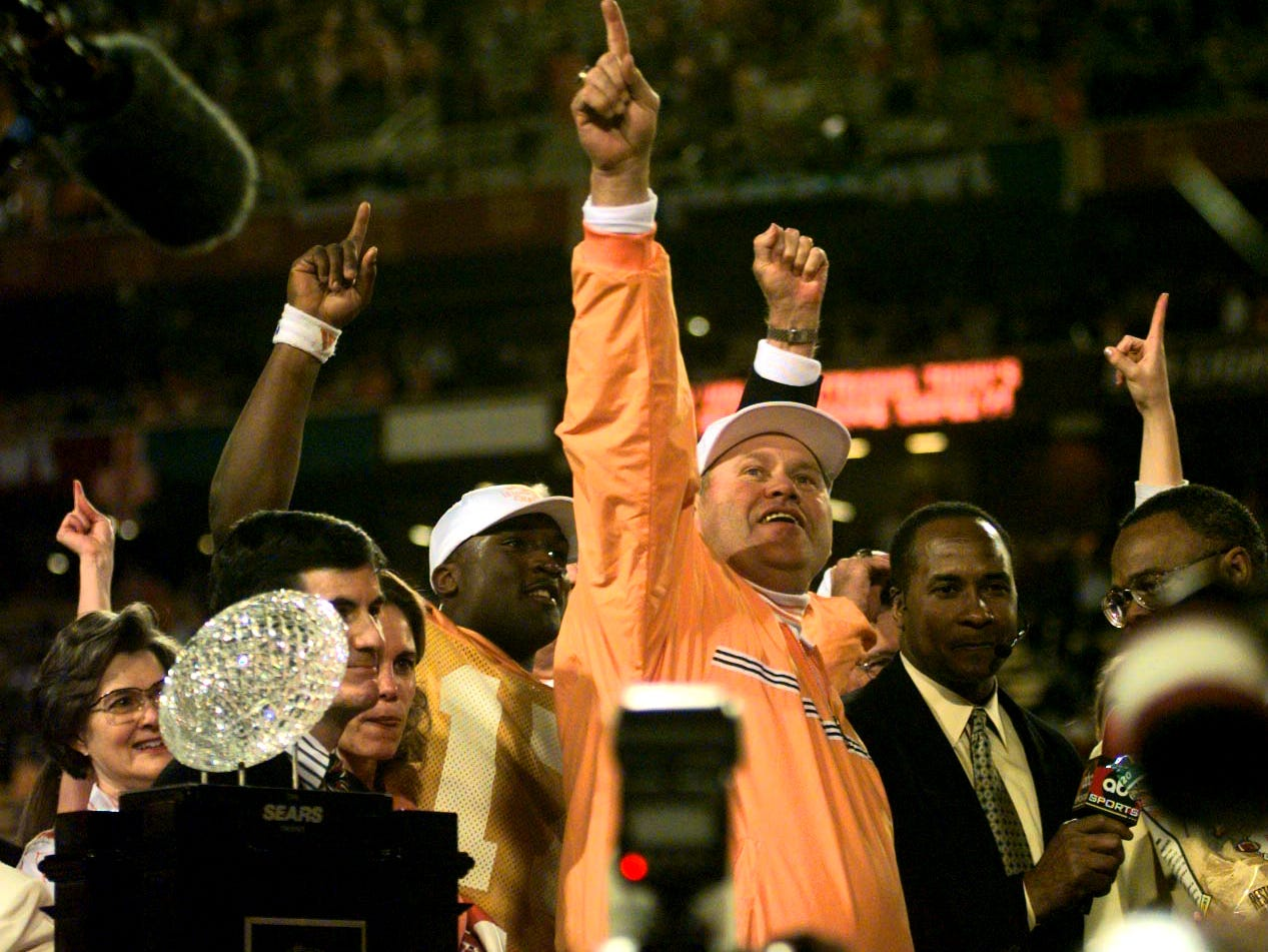 Tennessee's head coach Phil Fulmer celebrates on stage with Tee Martina behind him and the Sears National Championship trophy Jan. 5, 1999.