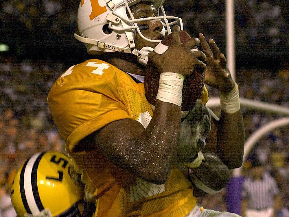 Tennessee's Cedric Wilson (14) catches a pass to make the score 30-31 in the final minutes of the game Saturday, Sept. 30, 2000. Hanging onto Wilson is 33- Demetrius Hookfin.
