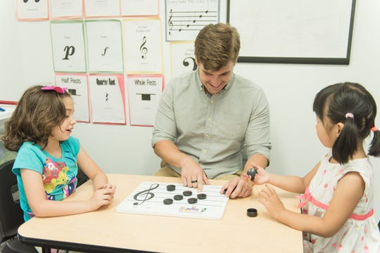 Music instructor Ryan King (center) works with Tamara Fadel (left) and Zhoujixiang Chen.
