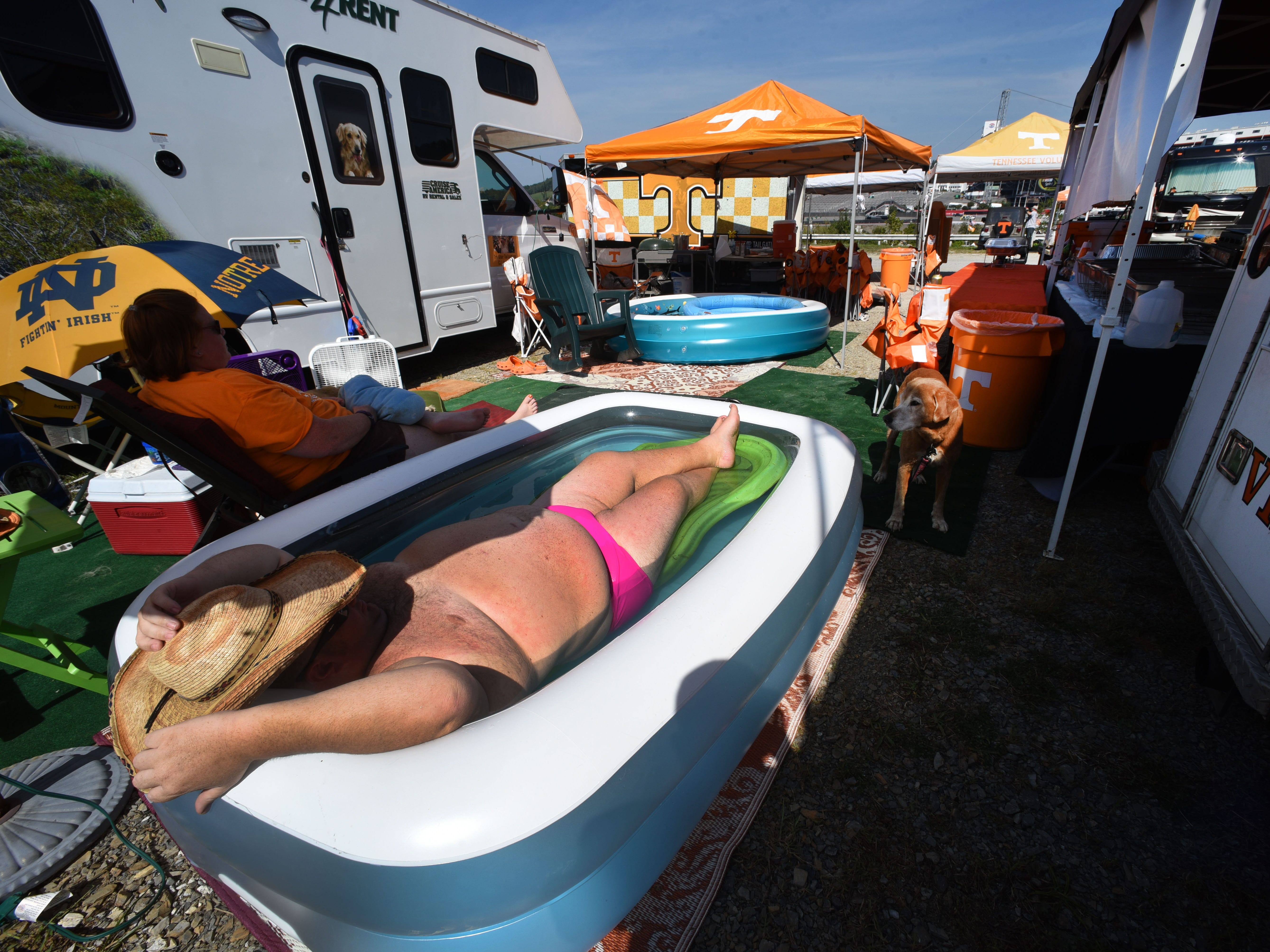 C.J. Jackson, cooling off in his pool, and his friend Kristen Kasko, left, from Tri-Star Tailgating arrived Thursday, September 8, 2016 to enjoy camping outside the Bristol Motor Speedway for the Battle At Bristol.