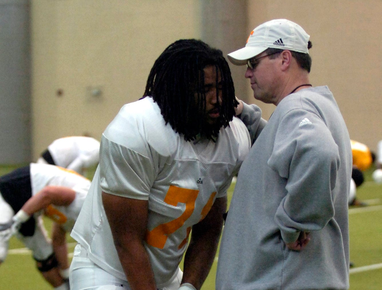 Offensive coordinator Jim Chaney talks with Dallas Thomas during warm-ups at spring practice on Tuesday.