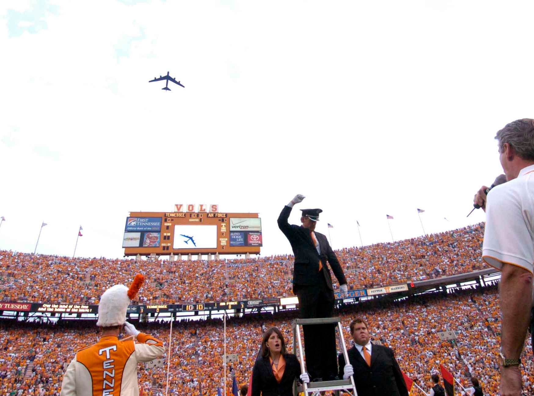 Andy Wentzel, right, sings the National Anthem as an Air Force B-52 Stratofortress does a fly over Saturday at Neyland Stadium. The B-52, commanded by Air Force Academy graduate Lt Col Kent Schultz, is from the 917th WingÕs 93rd Reserve Bomb Squadron, Barksdale AFB, Louisiana.