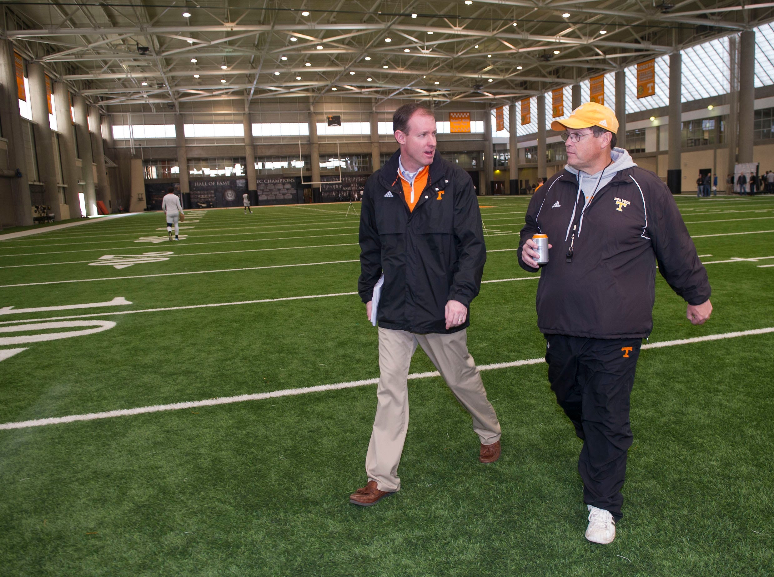 Jimmy Stanton, left Associate Athletic Director for Communications, and interim Head coach/offensive coordinator Jim Chaney walk across the indoor practice field in the Neyland-Thompson Sports Complex after Chaney spoke  with the Media after practice on Monday November 19, 2012 at the indoor practice field in the Neyland-Thompson Sports Complex.