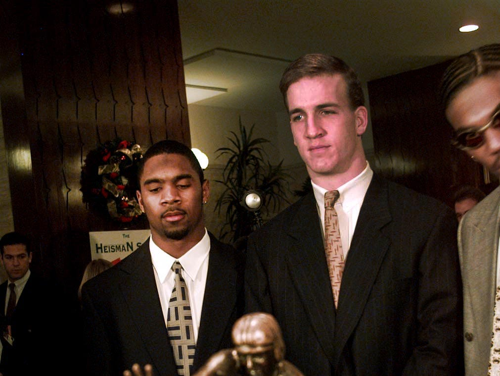 Charles Woodson and Peyton Manning pose with the Heisman Trophy at the Downtown Athletic Club Saturday night before the actual award was made. 1997.