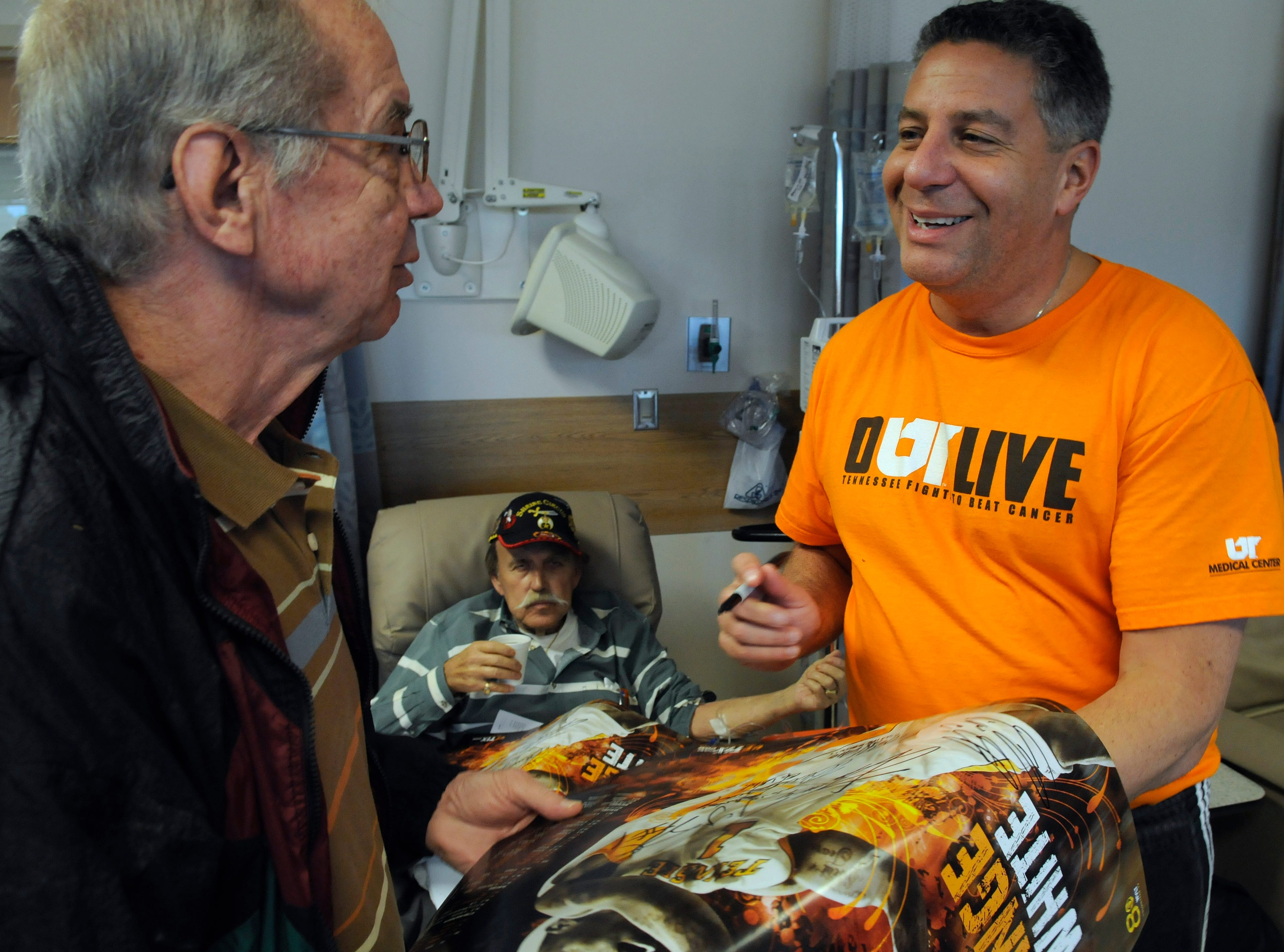 UT basketball head coach Bruce Pearl, right, jokes with Richard Jones, left, while signing a poster for Jones and his wife who was in the center. In the background is Glenn Smith who is getting his treatment at the institute. The UT coach team members visited patients at UT Medical Center Cancer Institute Wednesday, Dec 16, 2009 to talk and sign autographs.