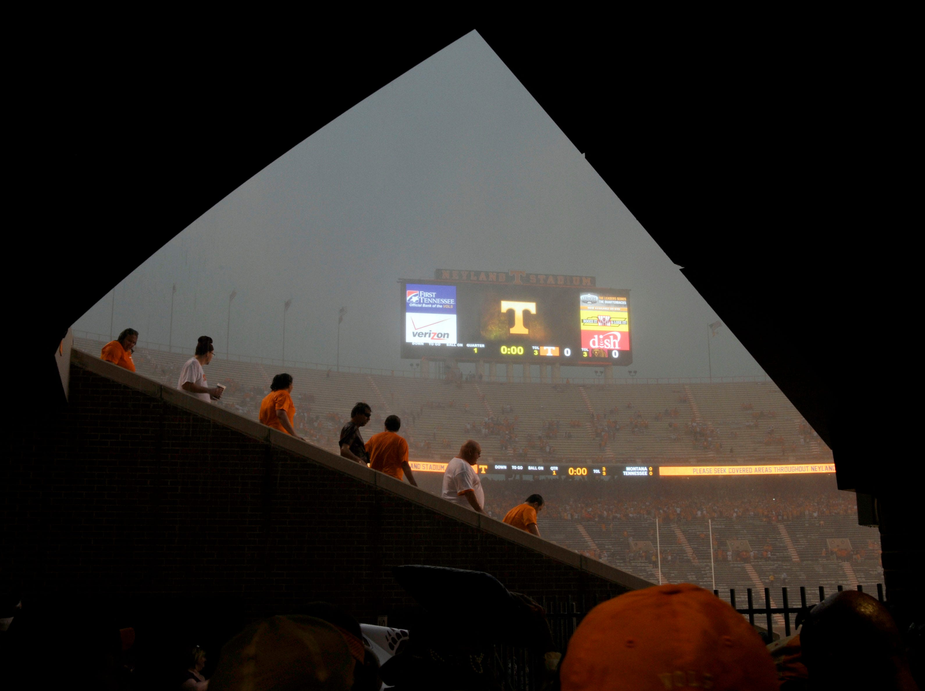 Fans leave the stands after heavy rain begins to fall in Neyland Stadium. About five minutes before the kickoff with the Montana Grizzlies Saturday, Sep. 3, 2011 in Neyland Stadium the game was delayed because of weather in the area.