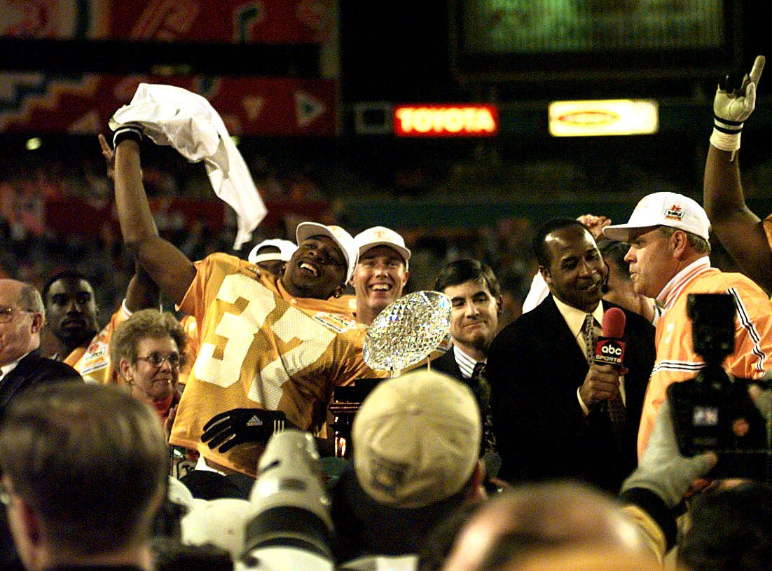Tennessee's Peerless Price celebrates and yells to the crowd as head coach Phil Fulmer talks to reporters on the award stand Monday, Jan. 4, 1999 after winning the National Championship.