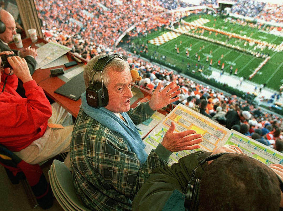 "John Ward talks to staff in the broadcast booth as the Tennessee football team runs through the ""T"". To the far left is Bill Anderson, Russ Bebb (red coat), John Ward (center) and spotter Randy O'Neal. 1998."