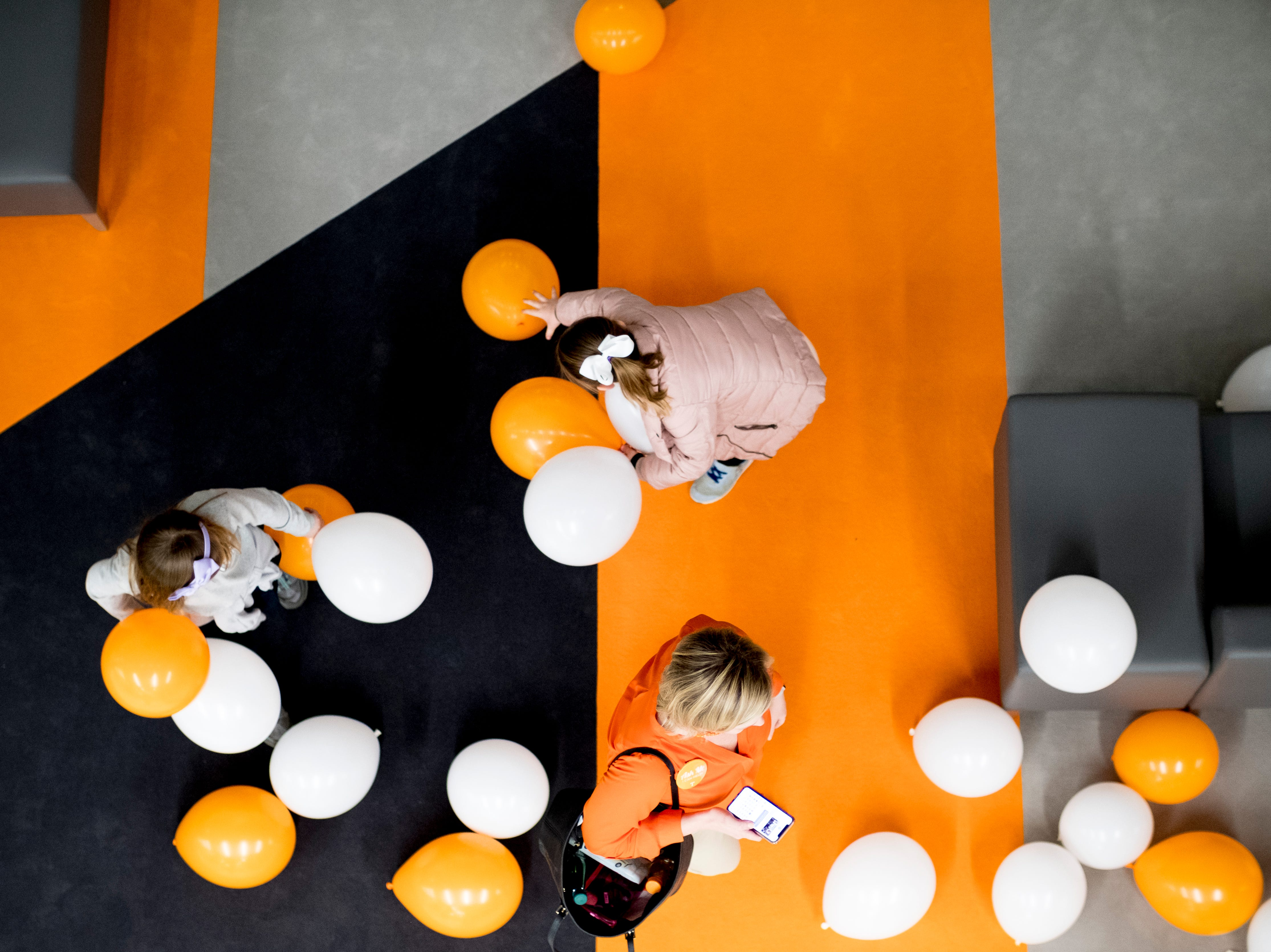 "Kids play with balloons during a lighting of the torchbearer celebration at the new UT Student Union in Knoxville, Tennessee on Tuesday, January 8, 2019. The blown glass ""flames"" were created by Knoxville expert glass blower Matthew Cummings of Pretentious Glass Co."