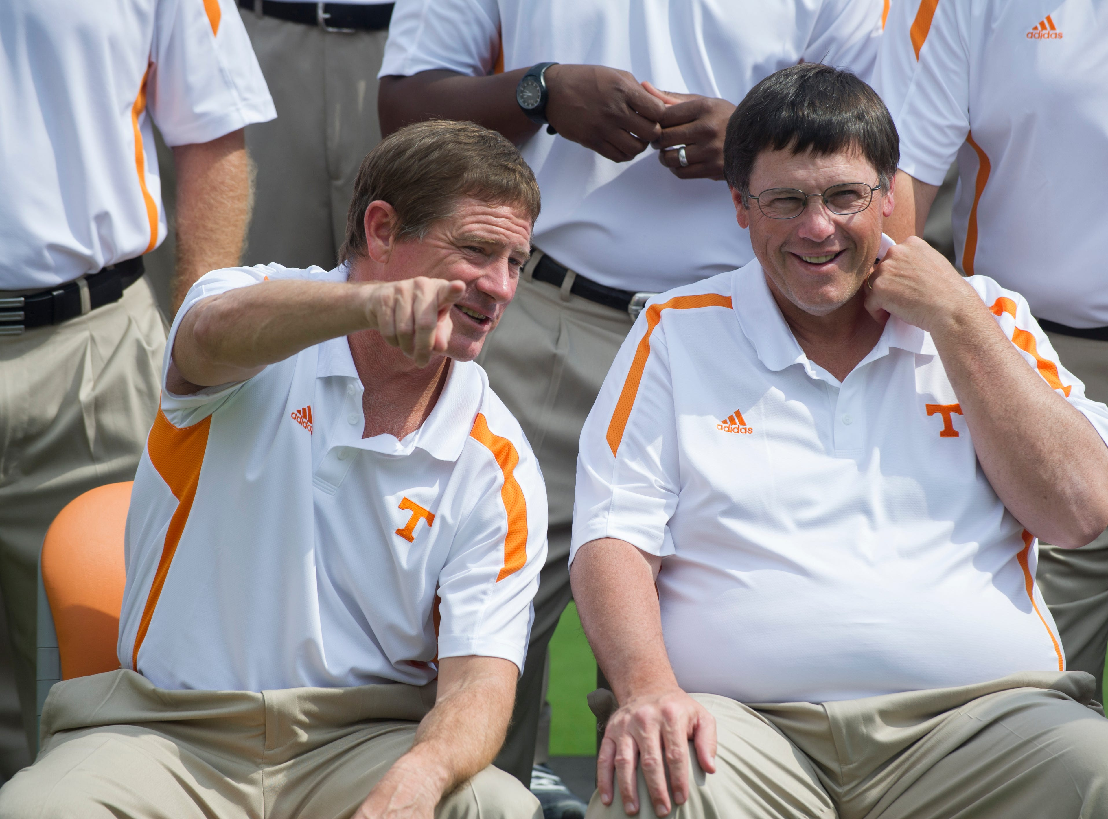 Tennessee special teams and tight ends coach Charlie Coiner, left, talks with offensive coordinator Jim Chaney as they pose for a group photo with the coaching staff during media day at Neyland Stadium Saturday, Aug. 18, 2012.