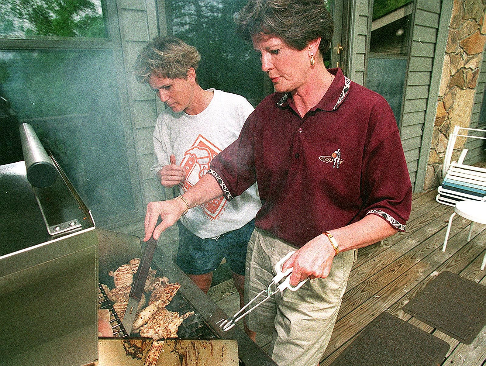 Lady Vols head coach Pat Summitt grills chicken on the back porch of her riverfront home for a team outing. With her is an assistant coach Holly Warlick 1996.