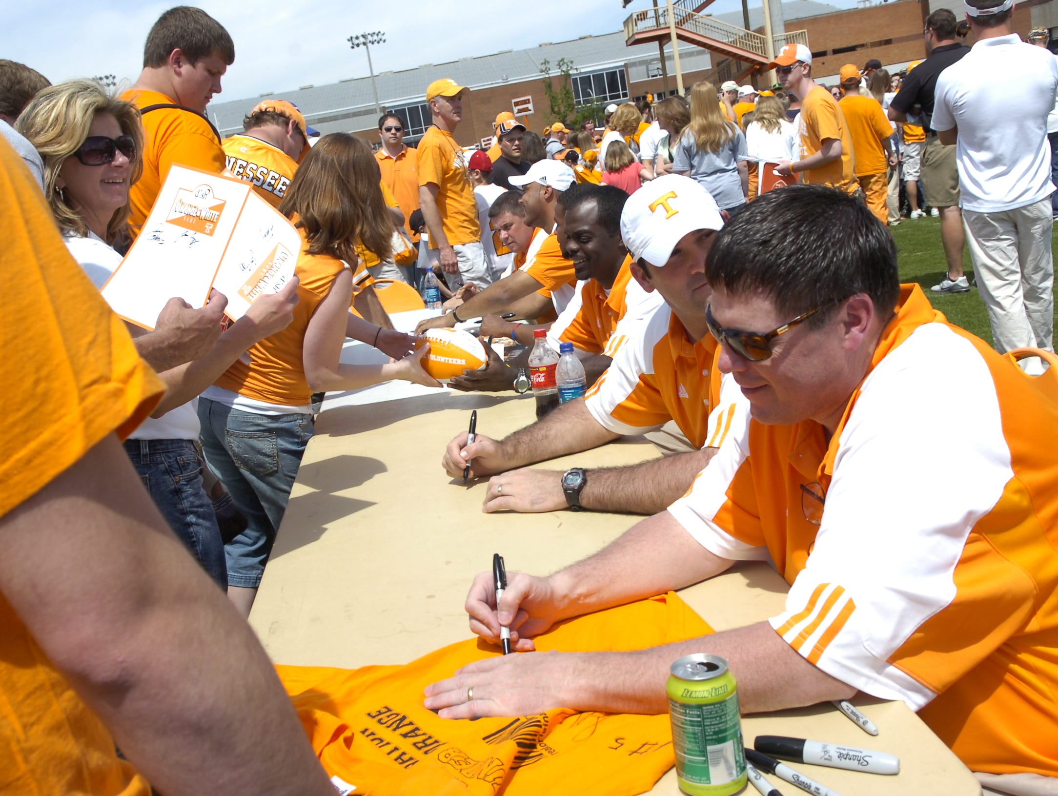 Offensive coordinator Jim Chaney signs autographs during Fan Day before the UT spring Orange and White football game on Saturday.