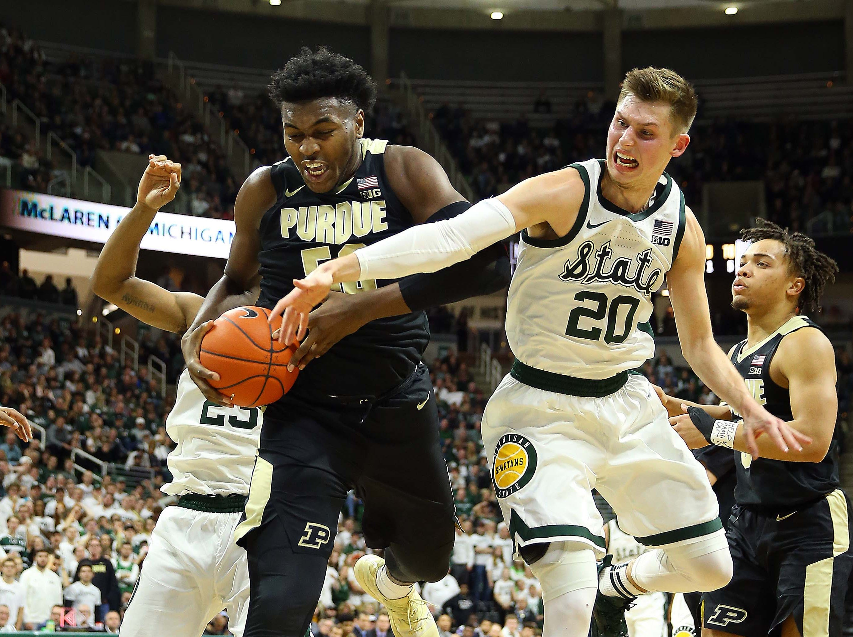 Jan 8, 2019; East Lansing, MI, USA; Purdue Boilermakers forward Trevion Williams (50) and Michigan State Spartans guard Matt McQuaid (20) fight for a loose ball during the second half of a game at the Breslin Center. Mandatory Credit: Mike Carter-USA TODAY Sports