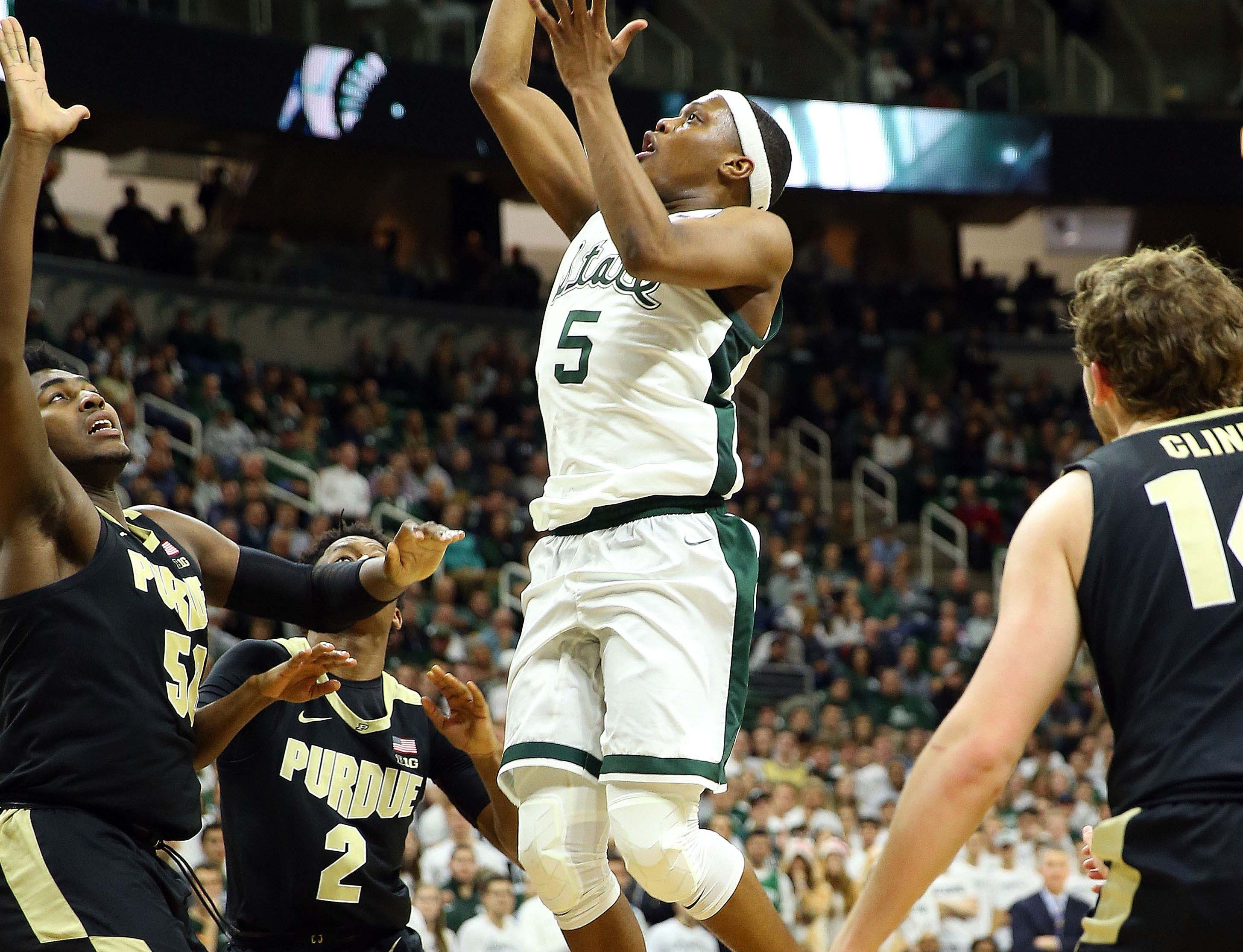 Jan 8, 2019; East Lansing, MI, USA; Michigan State Spartans guard Cassius Winston (5) is defended by Purdue Boilermakers forward Trevion Williams (50) and Purdue Boilermakers guard Eric Hunter Jr. (2) during the second half of a game at the Breslin Center. Mandatory Credit: Mike Carter-USA TODAY Sports