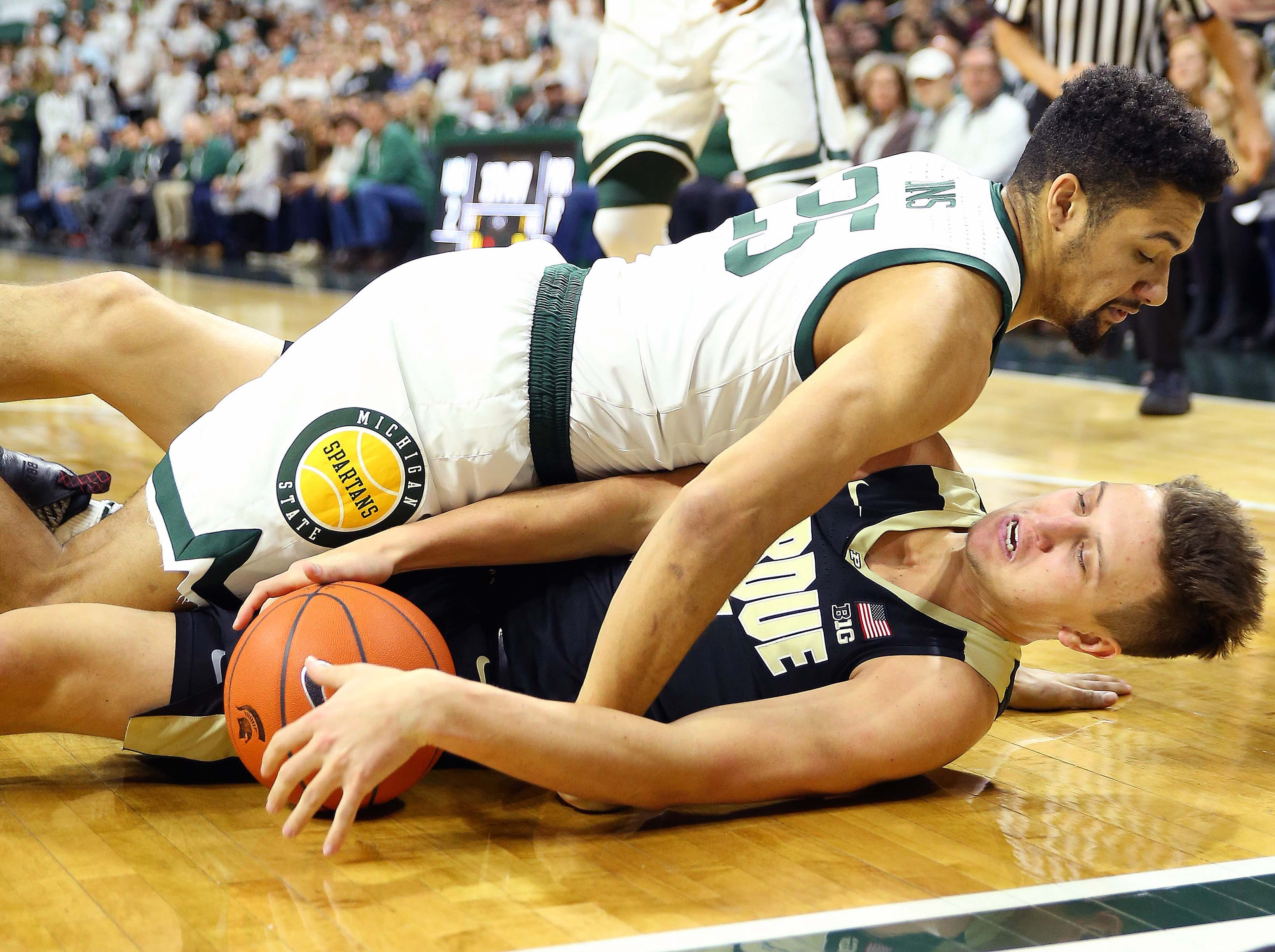 Jan 8, 2019; East Lansing, MI, USA; Purdue Boilermakers forward Aaron Wheeler (1) and Michigan State Spartans forward Kenny Goins (25) fight for a loose ball during the first half of a game at the Breslin Center. Mandatory Credit: Mike Carter-USA TODAY Sports