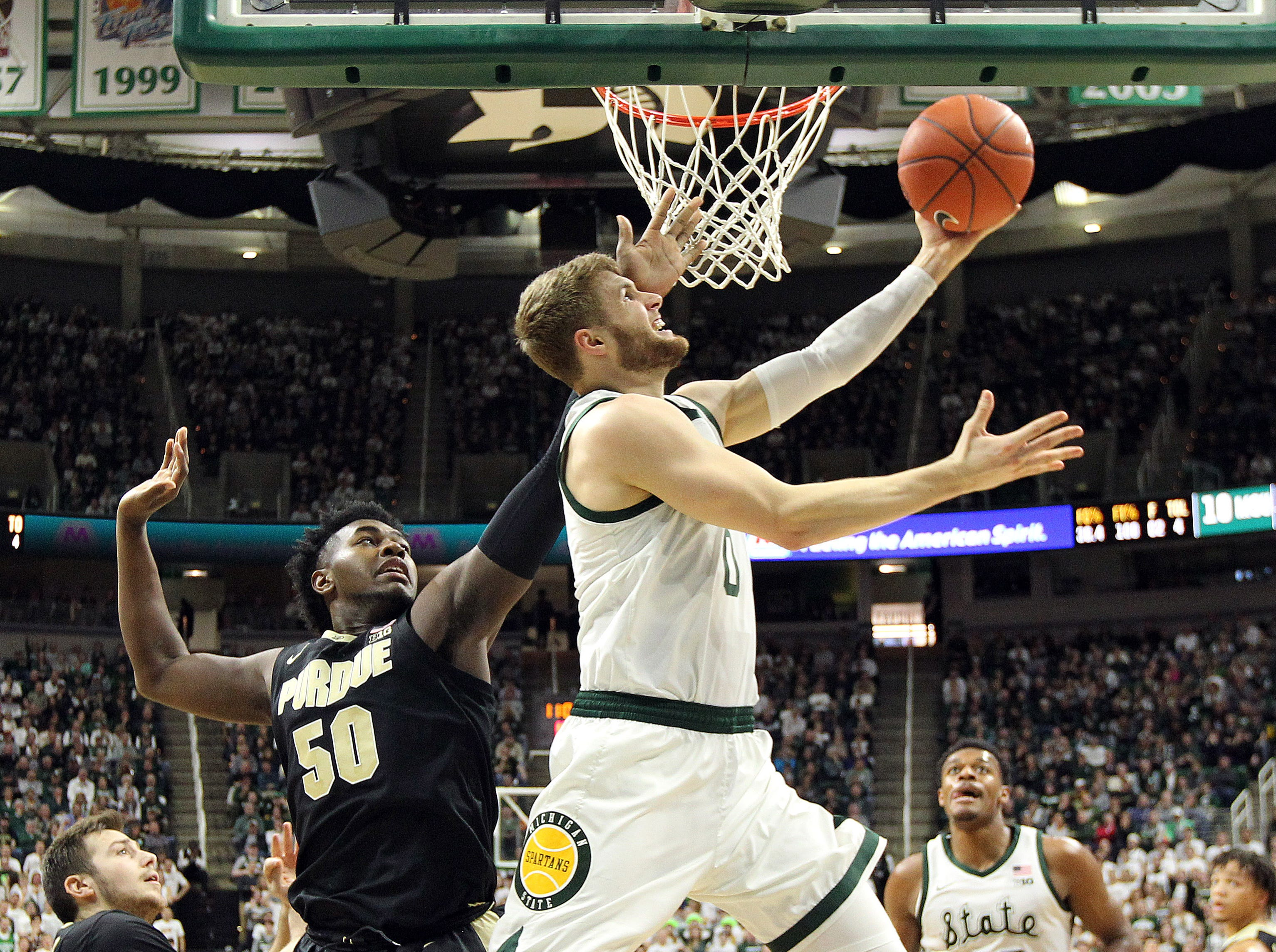 Jan 8, 2019; East Lansing, MI, USA; Michigan State Spartans forward Kyle Ahrens (0) lays the ball up in front of Purdue Boilermakers forward Trevion Williams (50) during the first half at the Breslin Center. Mandatory Credit: Mike Carter-USA TODAY Sports