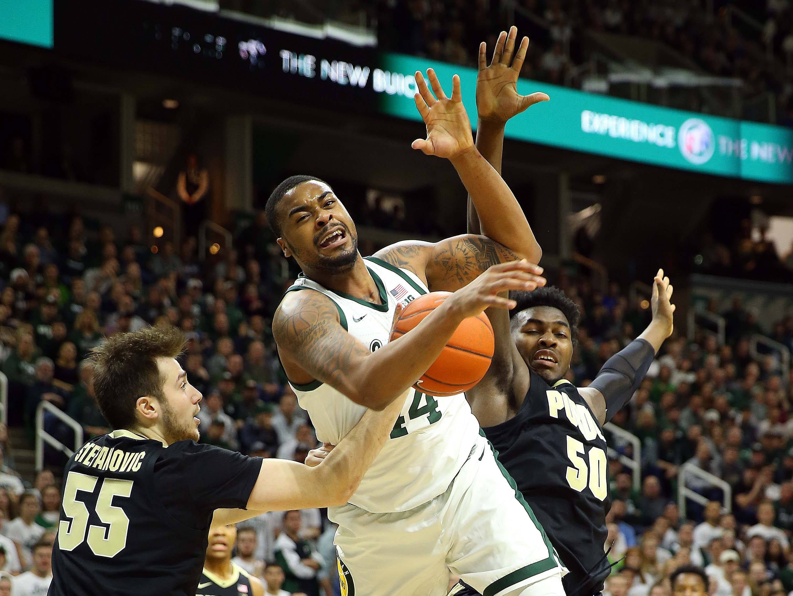 Jan 8, 2019; East Lansing, MI, USA; Michigan State Spartans forward Nick Ward (44) splits the defense of Purdue Boilermakers guard Sasha Stefanovic (55) and Purdue Boilermakers forward Trevion Williams (50) during the second half of a game at the Breslin Center. Mandatory Credit: Mike Carter-USA TODAY Sports