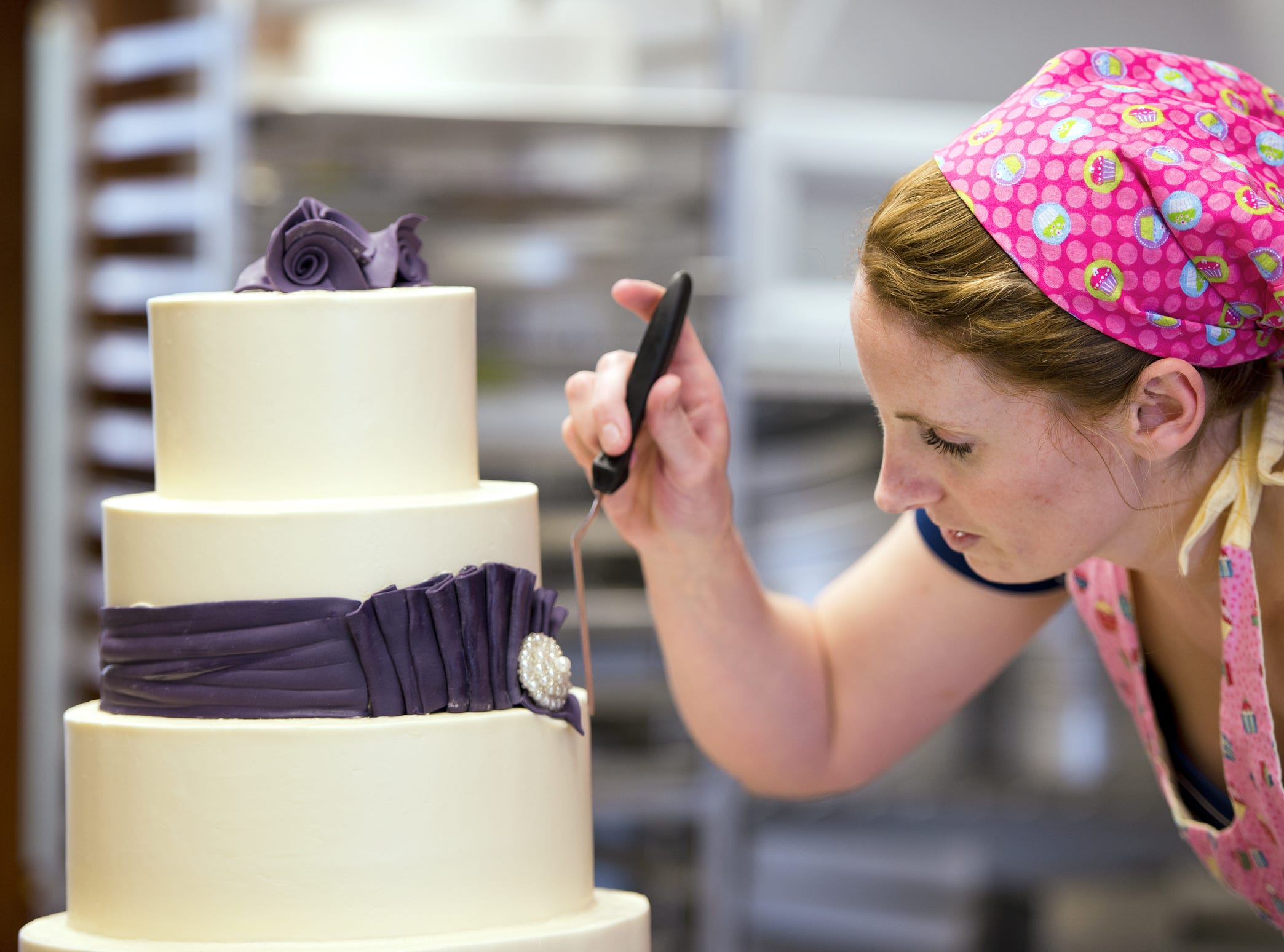 Something Blue Bakery owner Makenzie Kus works on a wedding cake at the store, in Lafayette, on Friday, May 31, 2013. Kus said that either bold colors or soft vintage cakes are currently popular.