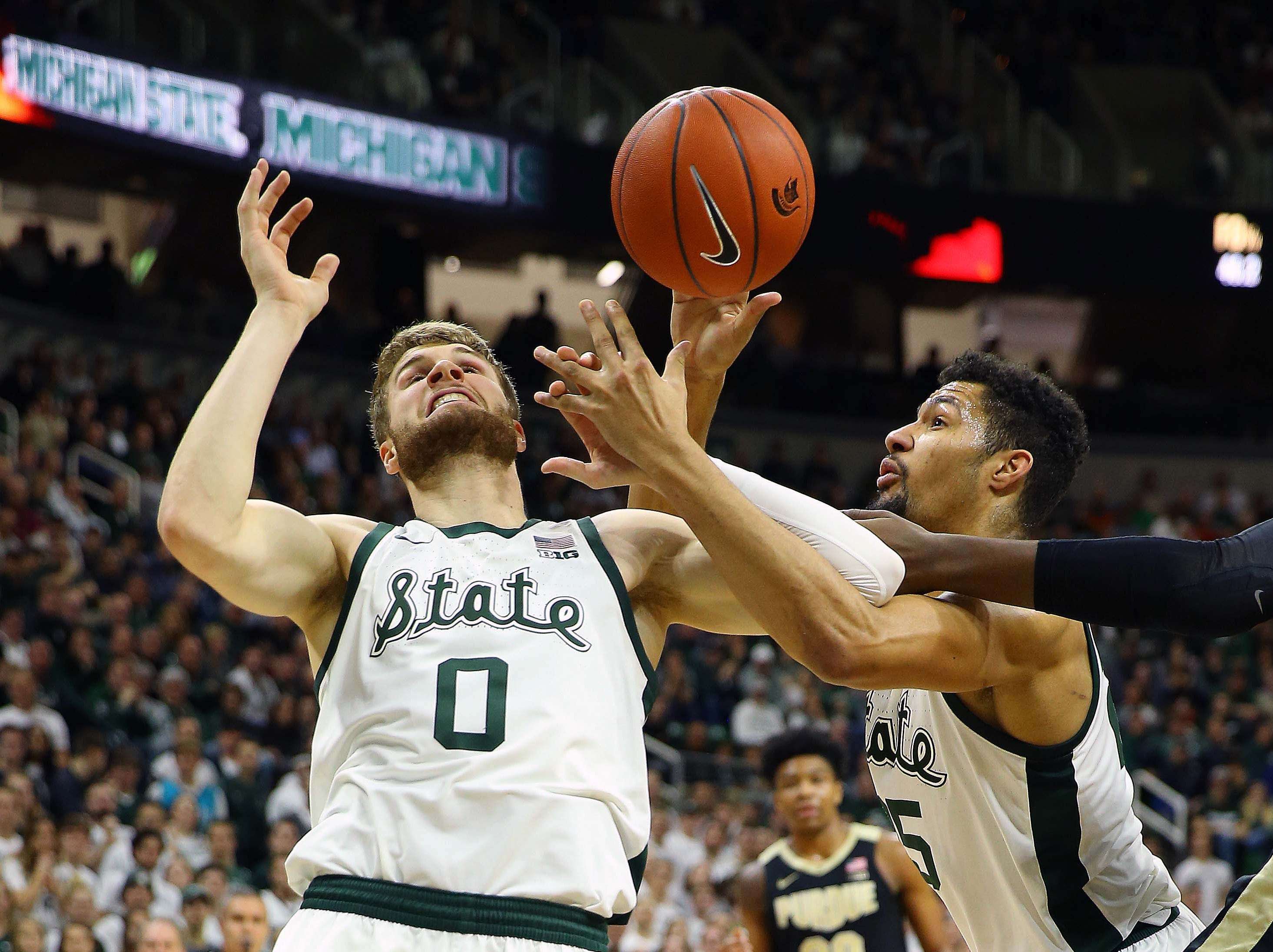 Jan 8, 2019; East Lansing, MI, USA; Michigan State Spartans forward Kyle Ahrens (0) and Michigan State Spartans forward Kenny Goins (25) fight for a loose ball during the first half of a game at the Breslin Center. Mandatory Credit: Mike Carter-USA TODAY Sports
