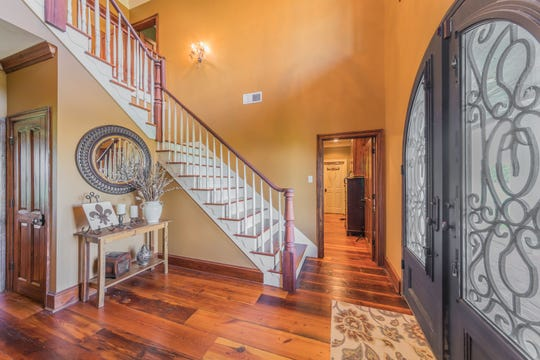 The grand entrance includes a beautiful staircase and wood floors.