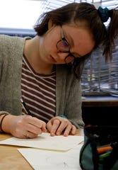 Abigail  Westfall draws illustrations for a children's book Wednesday, Jan. 9, 2019, at Lancaster High School in Lancaster. Senior art students at the school are illustrating a book written by Daisy Marcus.
