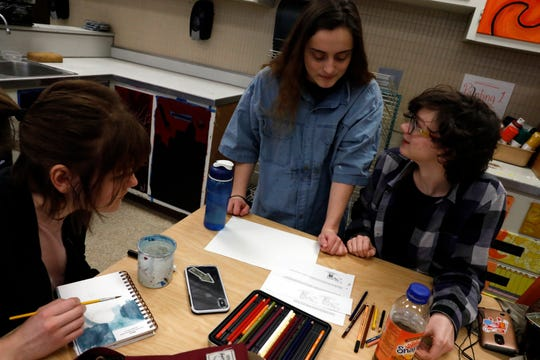 Bryanna Liptak, left, Autumn Brunney, center, and Carolina Sargent talk about Sargent's drawings for a children's book Wednesday, Jan. 9, 2019, at Lancaster High School in Lancaster. Senior art students at the school are illustrating a book written by Daisy Marcus.