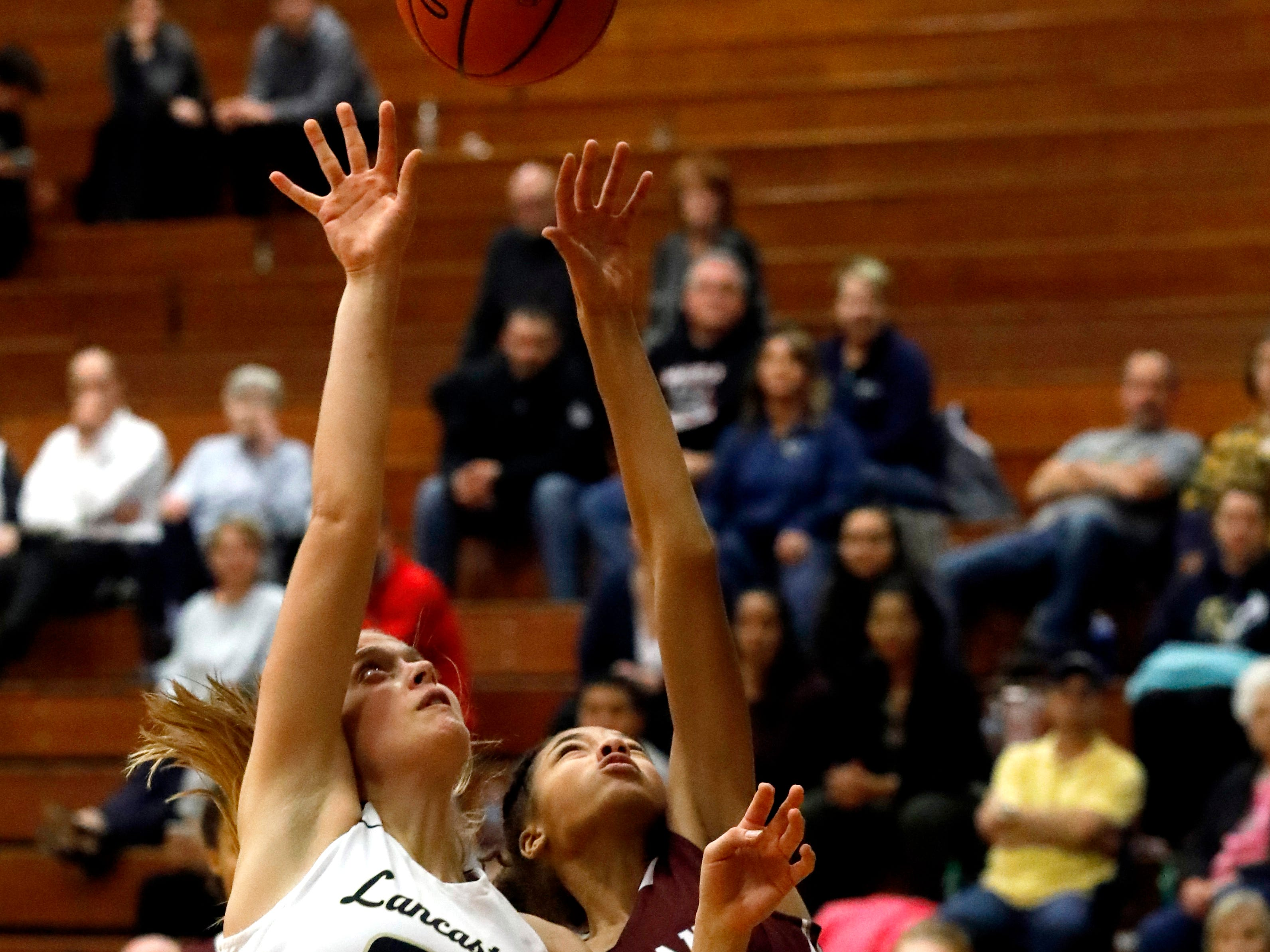 Lancaster's Anna Hartig and Canal Winchester's Kaylee DeShong fight for a rebound Tuesday night, Jan. 8, 2019, at Lancaster High School in Lancaster. The Golden Gales lost the game 50-40.