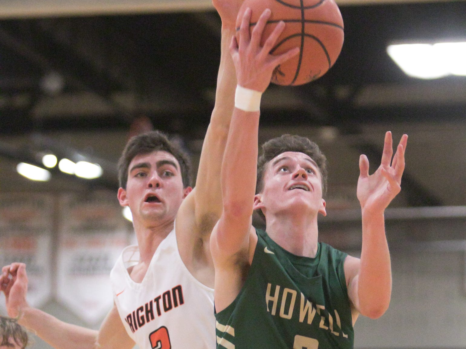 Howell's Kip French increases the Highlanders' lead in the third quarter of the game against Brighton Tuesday, Jan. 8, 2019, with Brighton's Nolan Ehman guarding him.