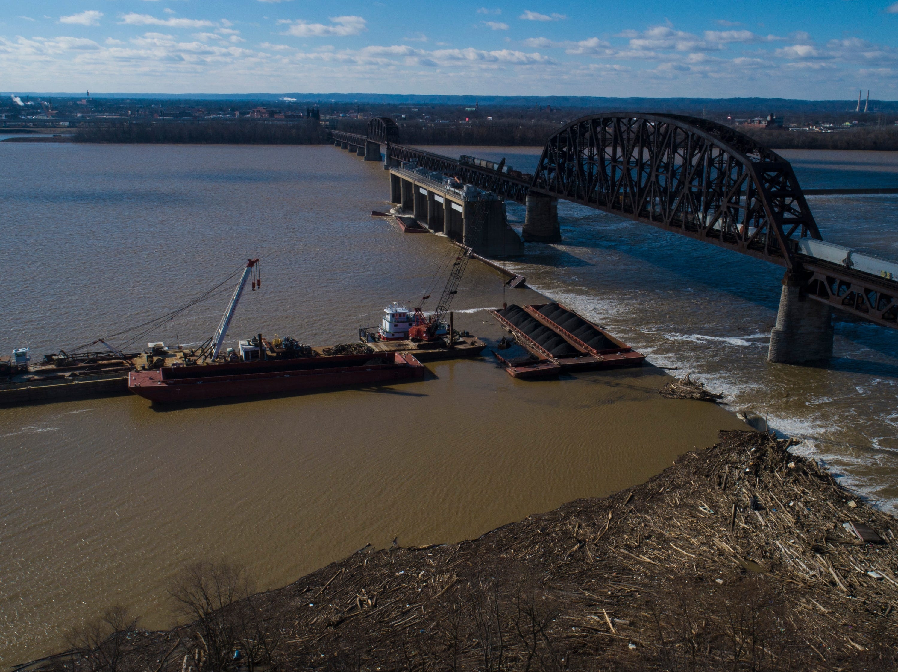 A crane lifts coal still remaining on the barges that are still afloat at the dam along the Ohio River on Wednesday morning. Once the coal is recovered from each barge, the barge will subsequently be recovered. The process is expected to take weeks. Jan. 9, 2019