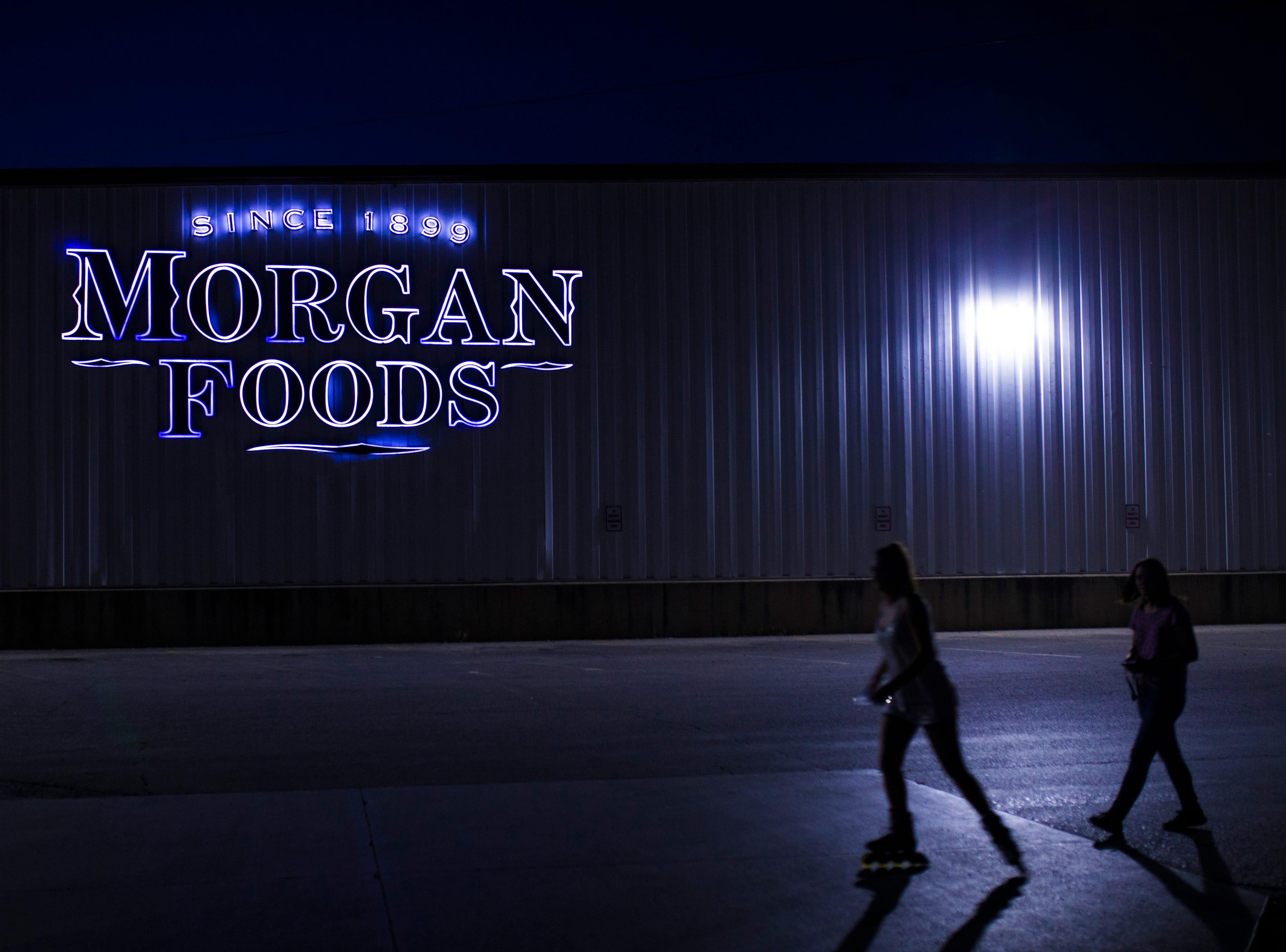 Teenagers make their way past the Morgan Foods canned goods factory in Austin, Indiana at night. Morgan Foods is the largest employer in the small town and has a history in the area going back to 1899. The canning factory is largely responsible for the large influx of Appalachian transplants that came from eastern Kentucky seeking work in the 1960s. As they journeyed from the hills to the flat farm land in rural Indiana, many also brought along generational poverty and low-education which play a role in Austin's HIV and drug epidemics. Aug. 12, 2018