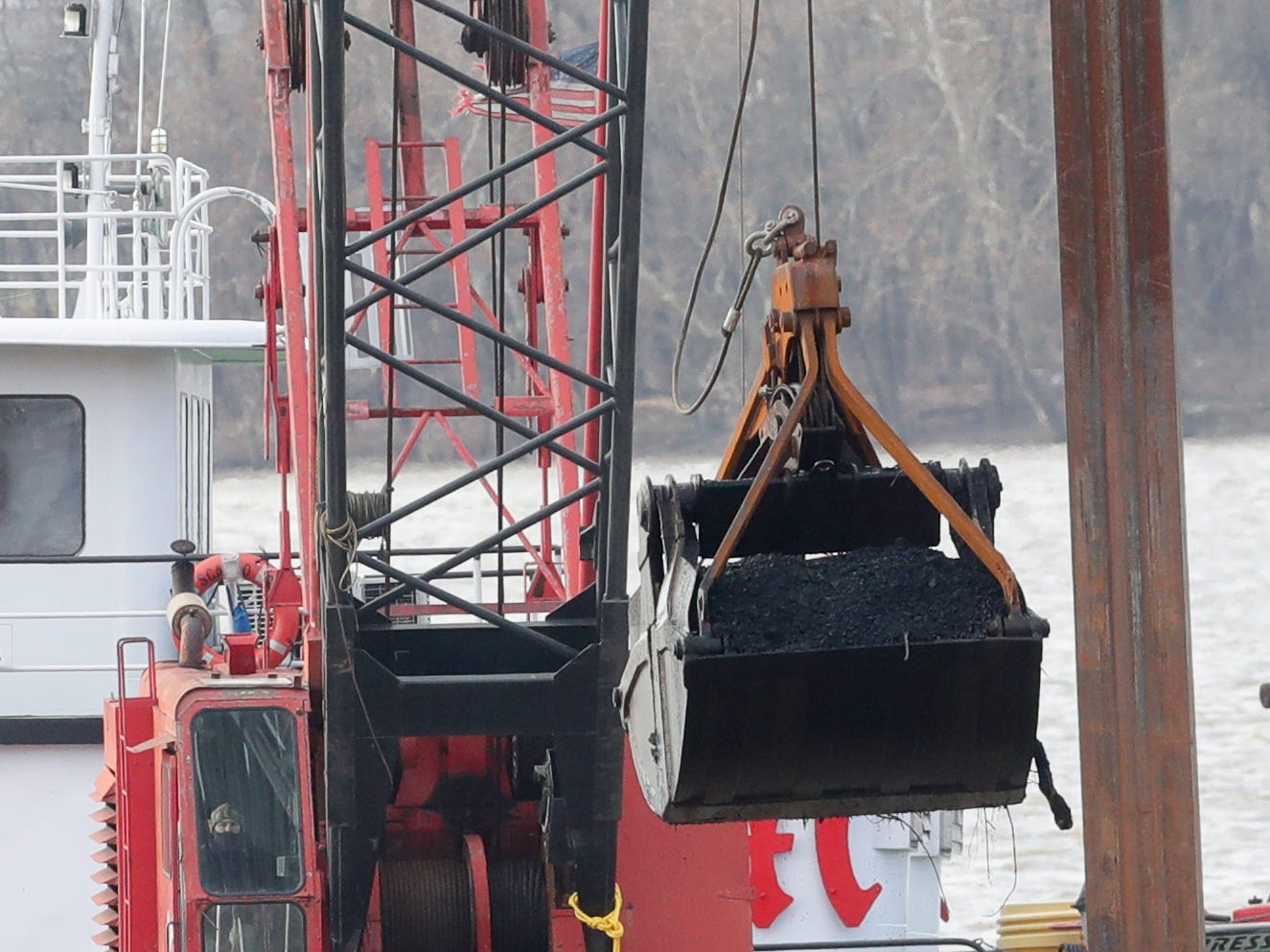 Salvage crews remove the coal still on the several barges that are stuck on the McAlpine Dam. 