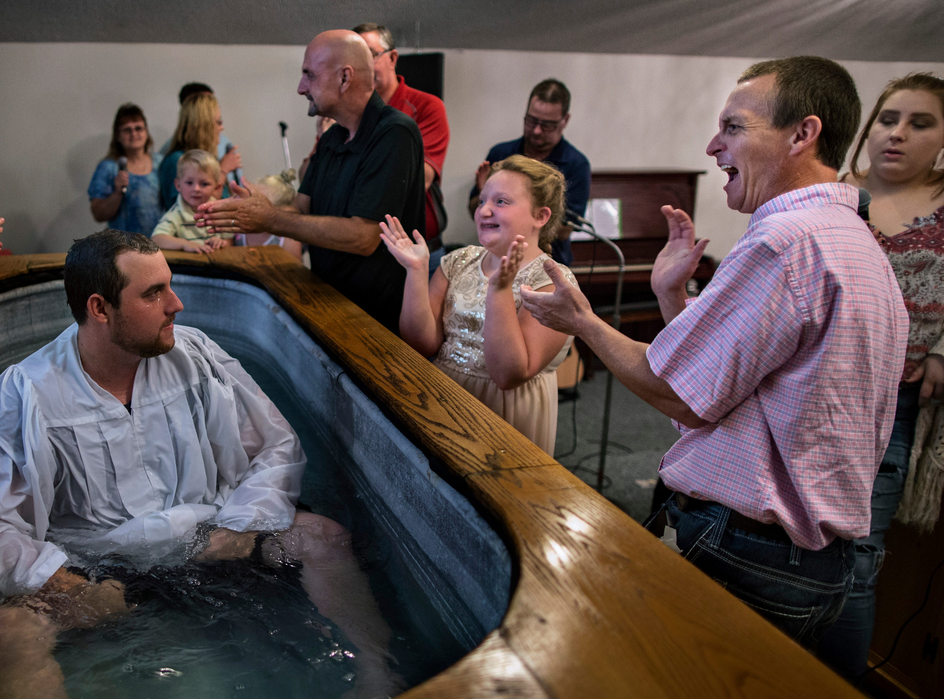 "Tyler Roberts, left, looks on as former addict and pastor of the Church of the New Covenant, Jacob Howell, reacts to his baptism. ""It's a holy experience to be a part of someone's renewal and starting a new life,"" Howell said. Howell used drugs in Austin's northside for years before he found himself homeless, without a job, and his family broken apart.  Now, he aims to be a beacon for others as he reclaims his life and preaches hopeAug. 12, 2018"