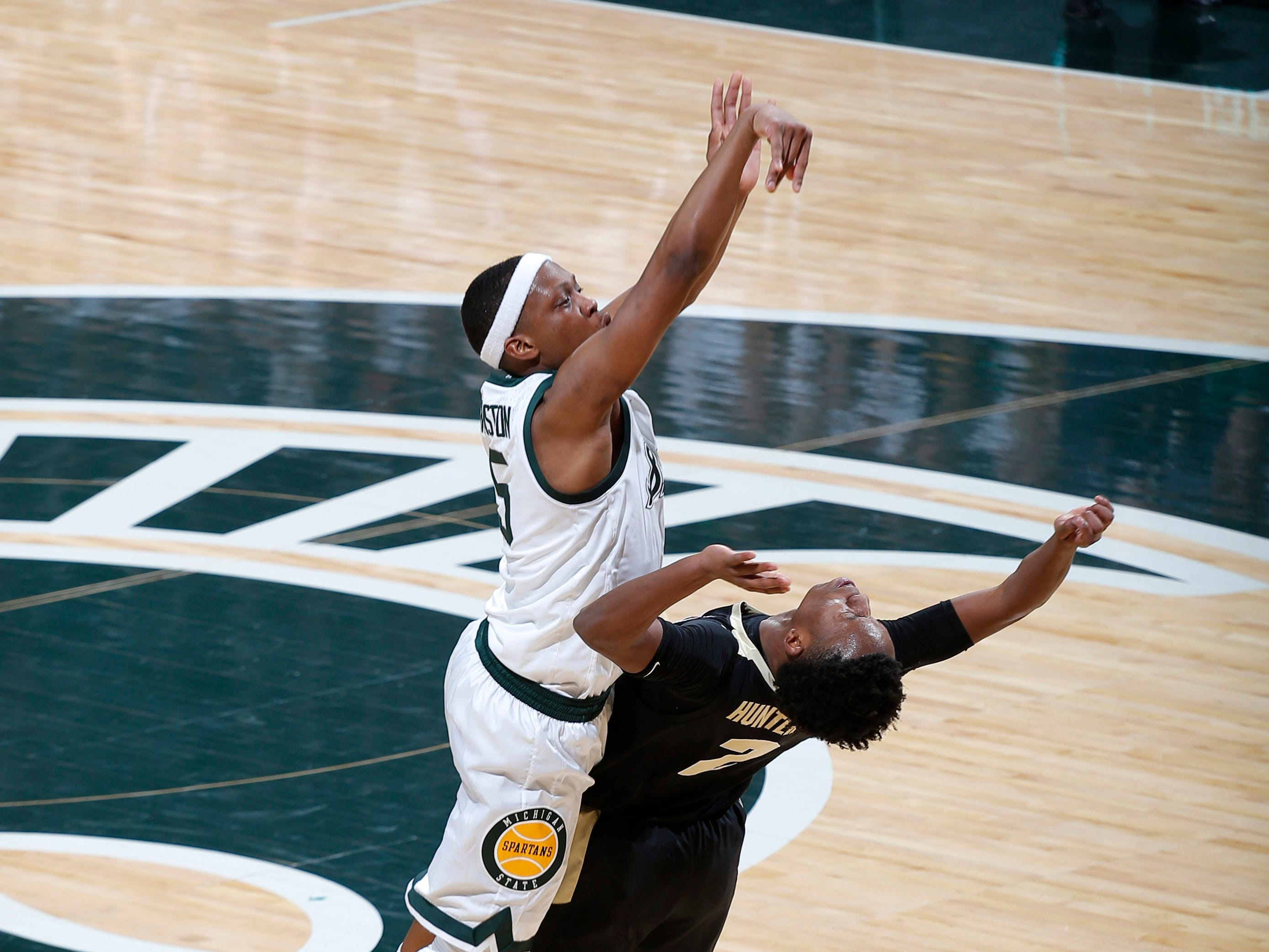 Michigan State's Cassius Winston, left, shoots over Purdue's Eric Hunter Jr. during the first half of an NCAA college basketball game, Tuesday, Jan. 8, 2019, in East Lansing, Mich.