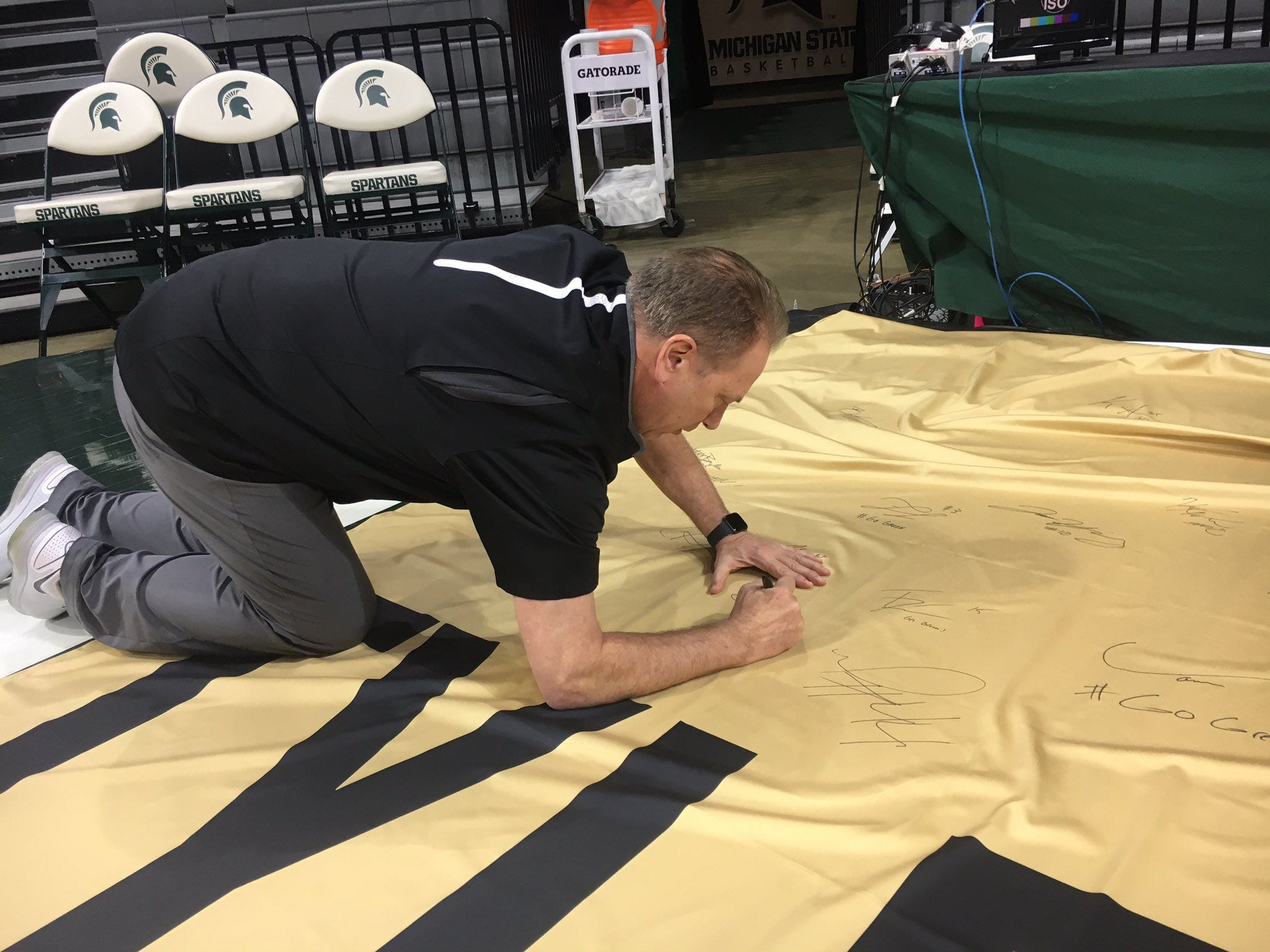 Michigan State men's basketball coach Tom Izzo signs a banner in remembrance of Purdue fan Tyler Trent ahead of the men's basketball game against Purdue on Jan. 8, 2019.
