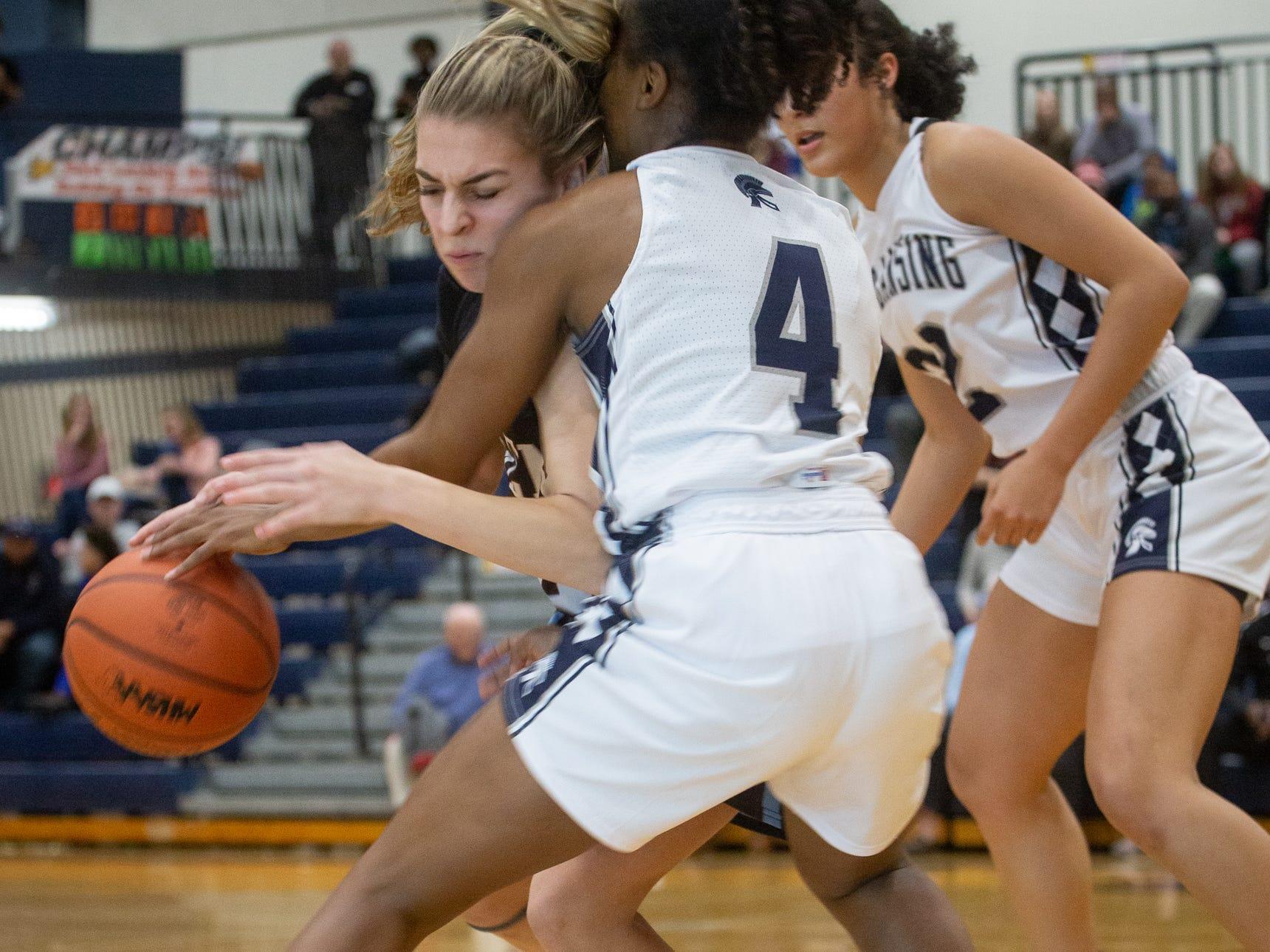 East Lanisng Junior, Sanaya Gregory tries to steal the ball from Okemos Sophomore, Lexie Sermak, Tuesday, Jan. 8, 2019 at East Lansing High School.
