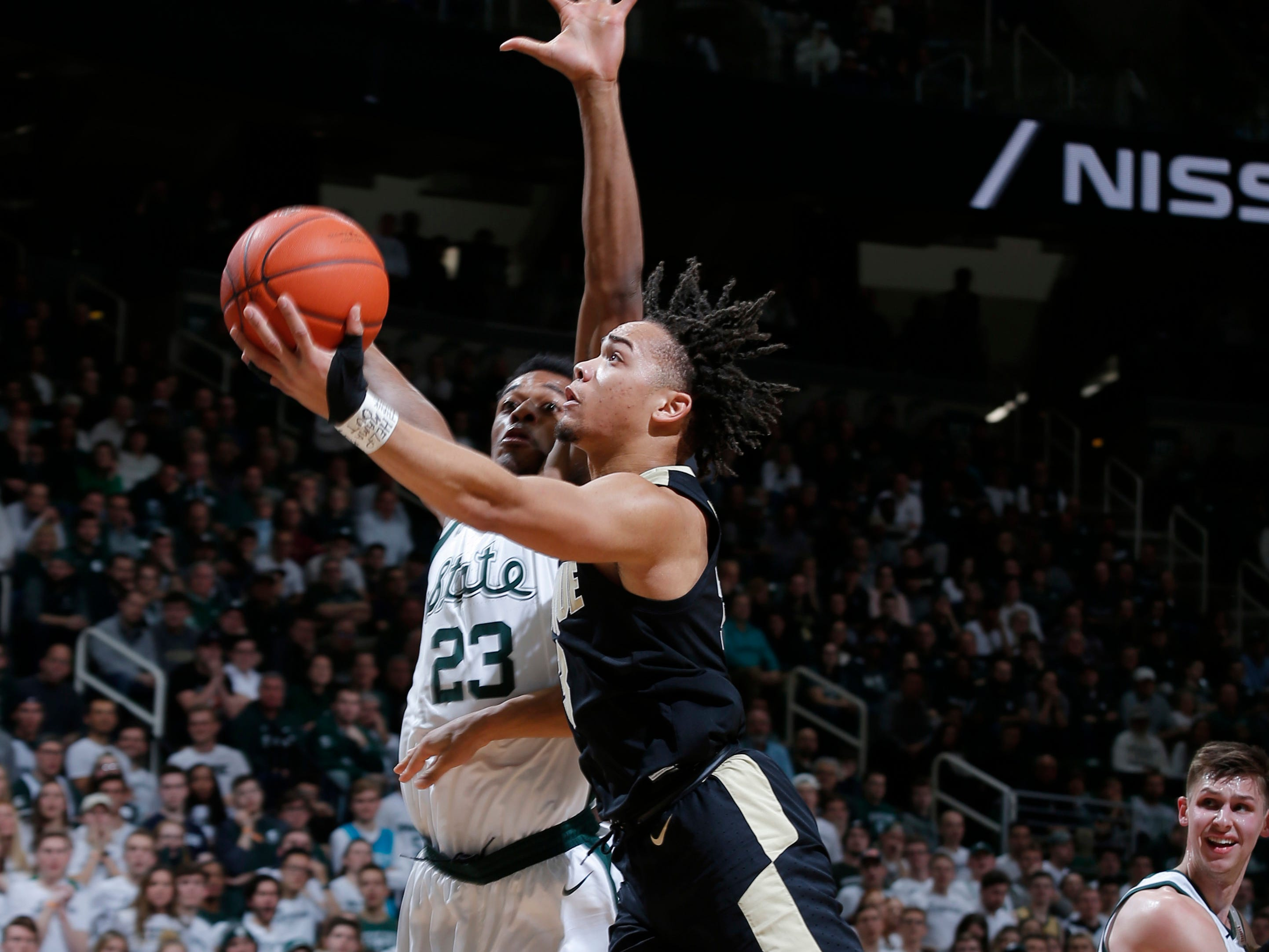 Purdue's Carsen Edwards, front, drives for a layup against Michigan State's Xavier Tillman (23) during the first half of an NCAA college basketball game, Tuesday, Jan. 8, 2019, in East Lansing, Mich.