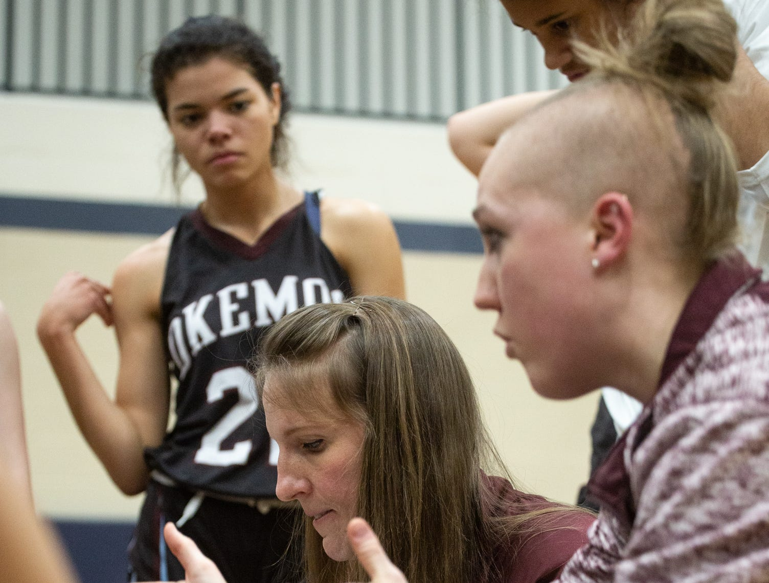 Okemos Coaches, Kristen Rasmussen and Megan Williams talk strategy with Chieftens during timeout, Tuesday, Jan. 8, 2019, at East Lansing High School.