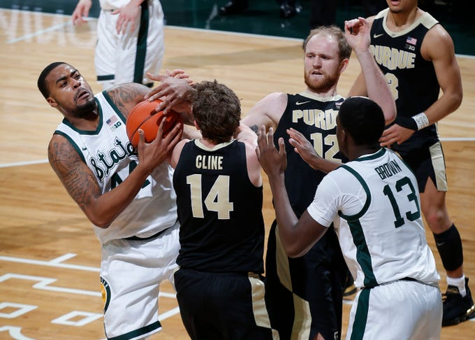 Michigan State's Nick Ward, left, and Gabe Brown (13) and Purdue's Ryan Cline (14) and Evan Boudreaux battle for the ball during the first half of an NCAA college basketball game, Tuesday, Jan. 8, 2019, in East Lansing, Mich.